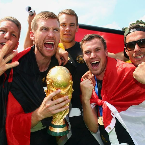 Germany's Bastian Schweinsteiger, Per Mertesacker, Manuel Neuer, Kevin Grosskreutz and Lukas Podolski (L-R) pose with the World Cup trophy during celebrations to mark the team's 2014 Brazil World Cup victory, at a 'fan mile' public viewing zone in Berlin July 15, 2014.  Germany's victorious soccer team led by coach Joachim Loew returned home on Tuesday after winning the 2014 Brazil World Cup. A triumphant Germany team landed in Berlin on Tuesday to a hero's welcome, greeted by hundreds of thousands of jubilant Germans waving flags and wearing the national colours, revelling in the nation's fourth World Cup victory on Sunday in Brazil.          REUTERSAlex Grimm/Pool (GERMANY - Tags: SPORT SOCCER WORLD CUP) - RTR3YRMX