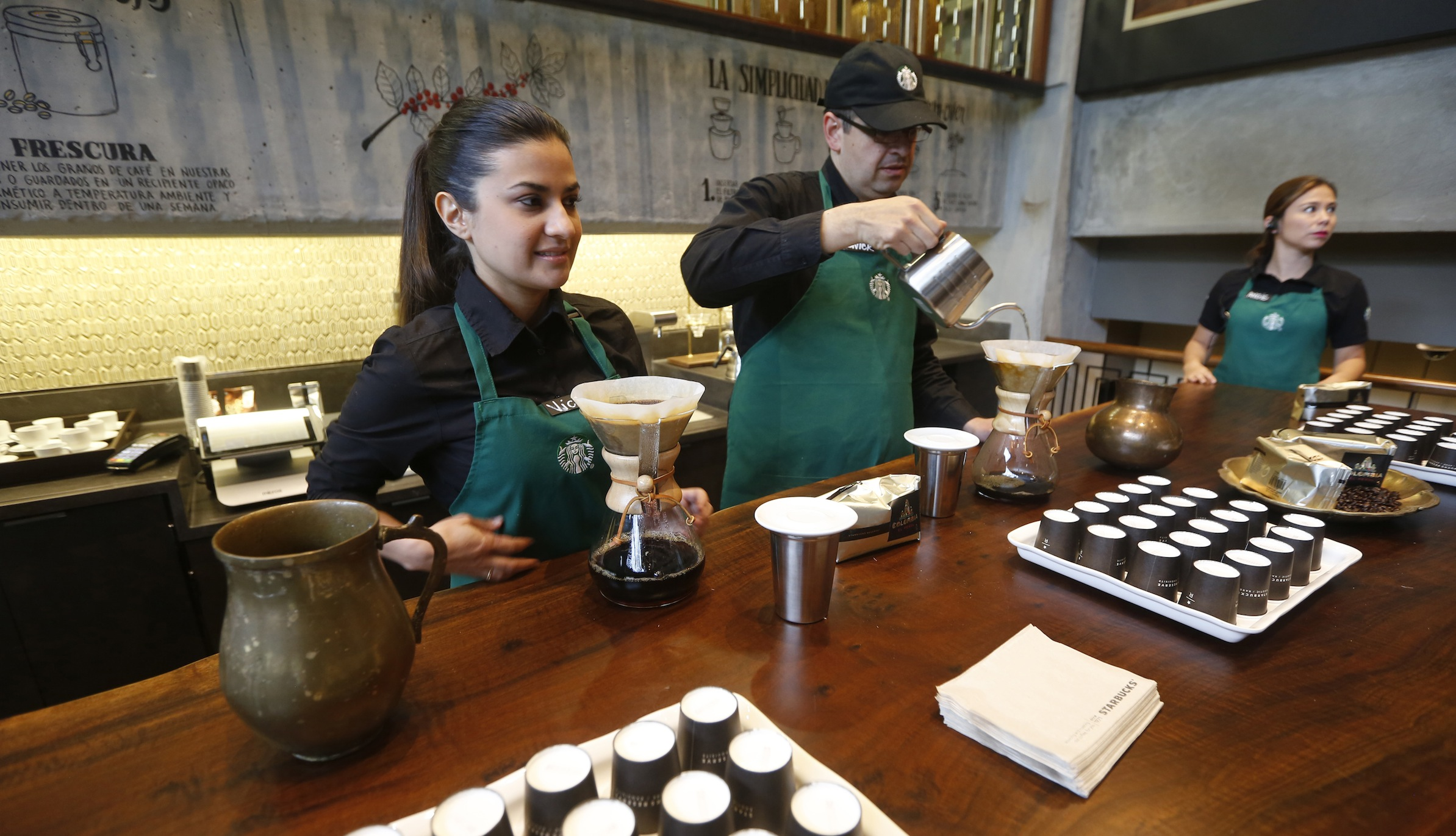 Workers prepare coffee during the inauguration of Starbuck's first Colombian store at 93 park in Bogota July 16, 2014. Starbucks Corp opened its first shop in Colombia on Wednesday, 43 years after the world's biggest coffee chain first started buying beans from the country famous for its premium arabica coffee named after fictional coffee farmer Juan Valdez. REUTERS/John Vizcaino (COLOMBIA - Tags: BUSINESS) - RTR3YXUW