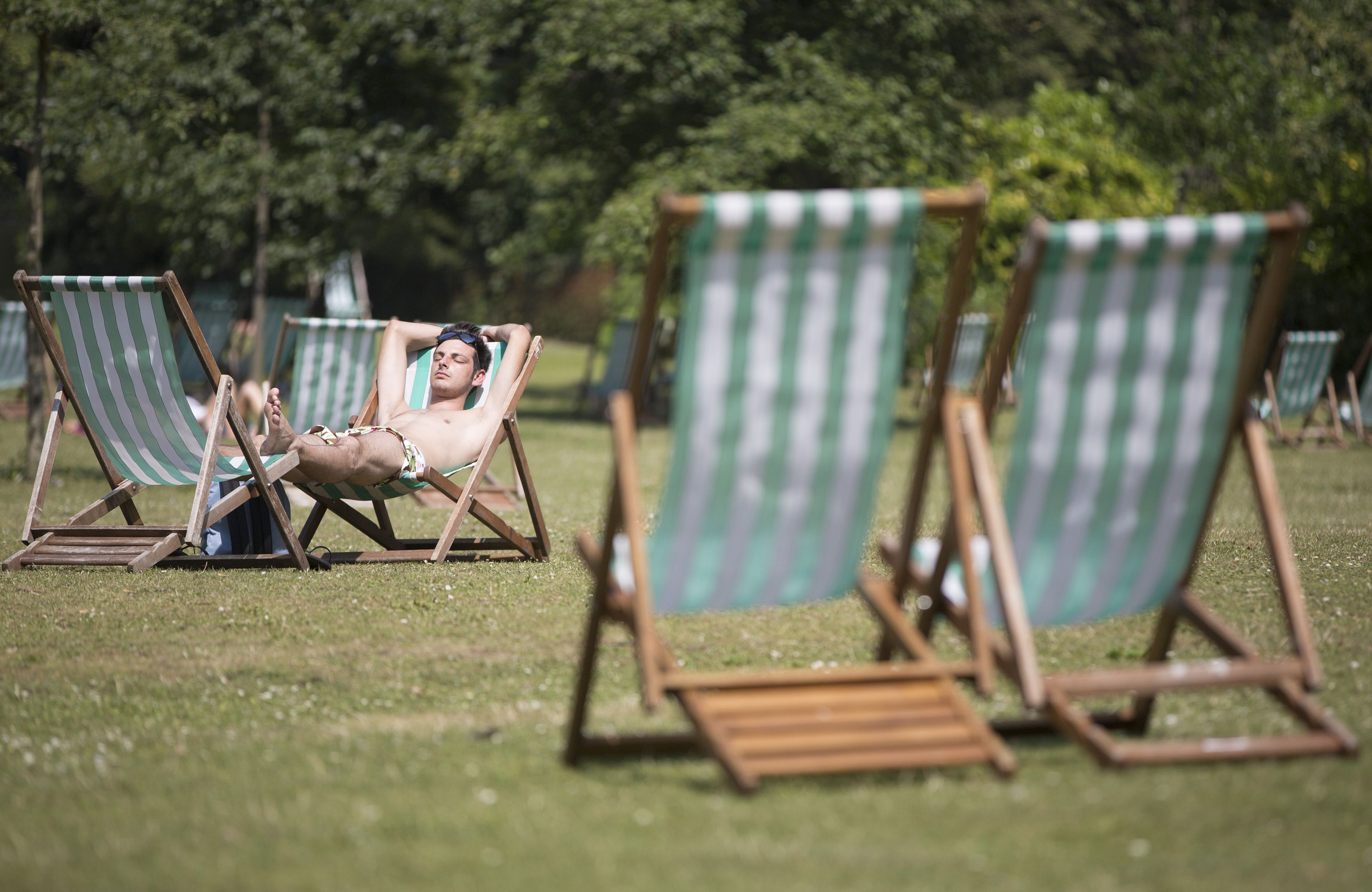 A man relaxes on a deckchair in Regents Park during a hot day in London July 18, 2014. REUTERS/Neil Hall