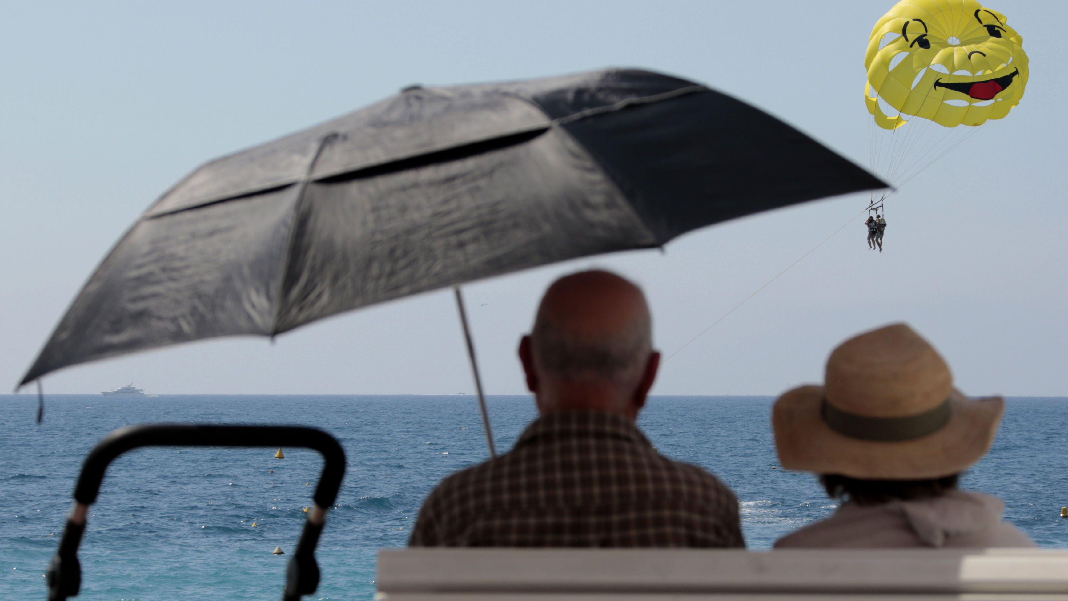 Two elderly people sit on a bench as they look at a parascending during a sunny summer day in Nice, southeastern France, July 28, 2014. REUTERS/Eric Gaillard (FRANCE - Tags: ENVIRONMENT TRAVEL SOCIETY)