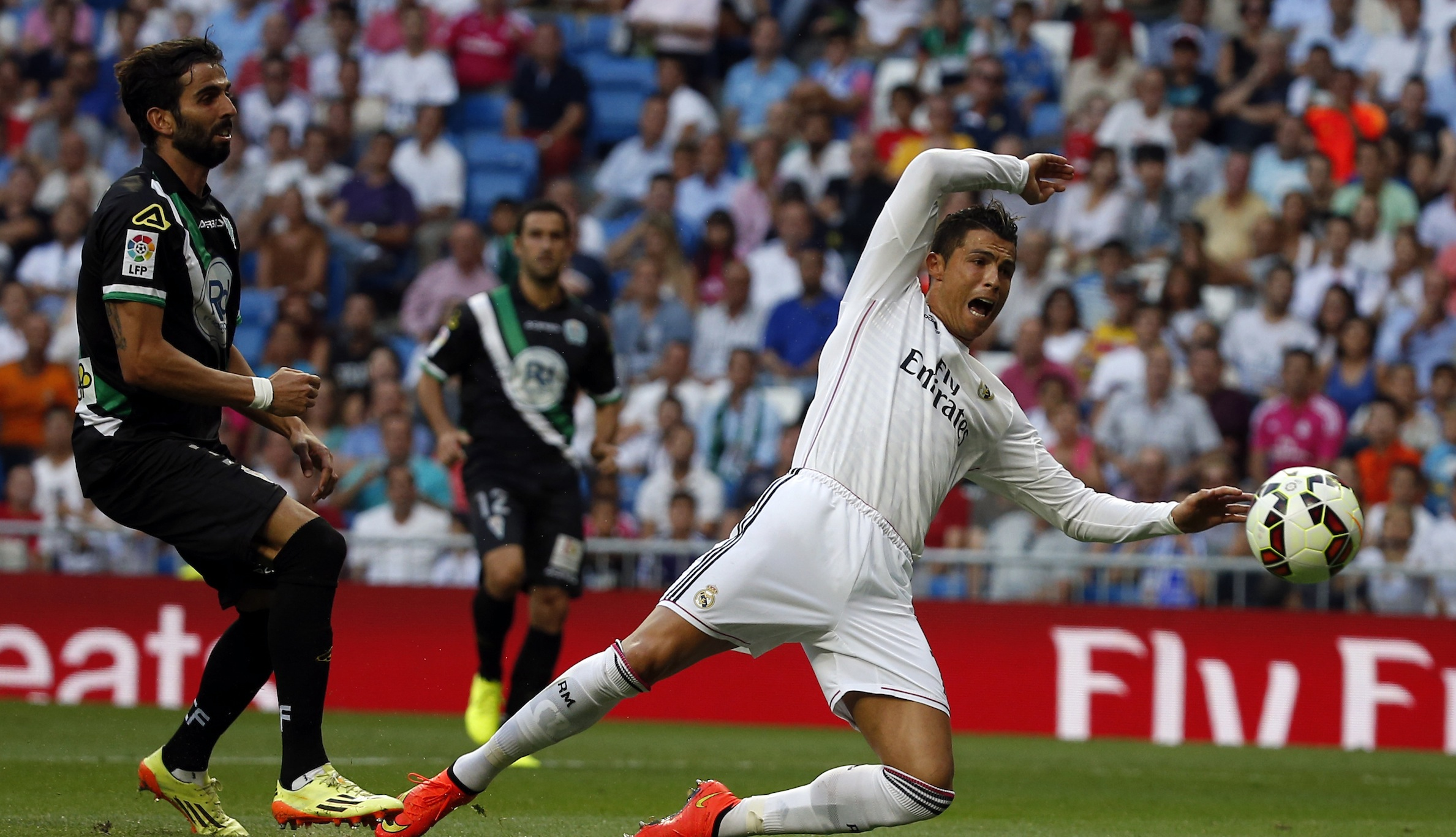 Real Madrid's Cristiano Ronaldo (R) falls inside the penalty area after being pushed by Cordoba's Angel Crespo during their Spanish first division soccer match at Santiago Bernabeu stadium in Madrid August 25, 2014.  REUTERS/Sergio Perez (SPAIN - Tags: SPORT SOCCER) - RTR43P37
