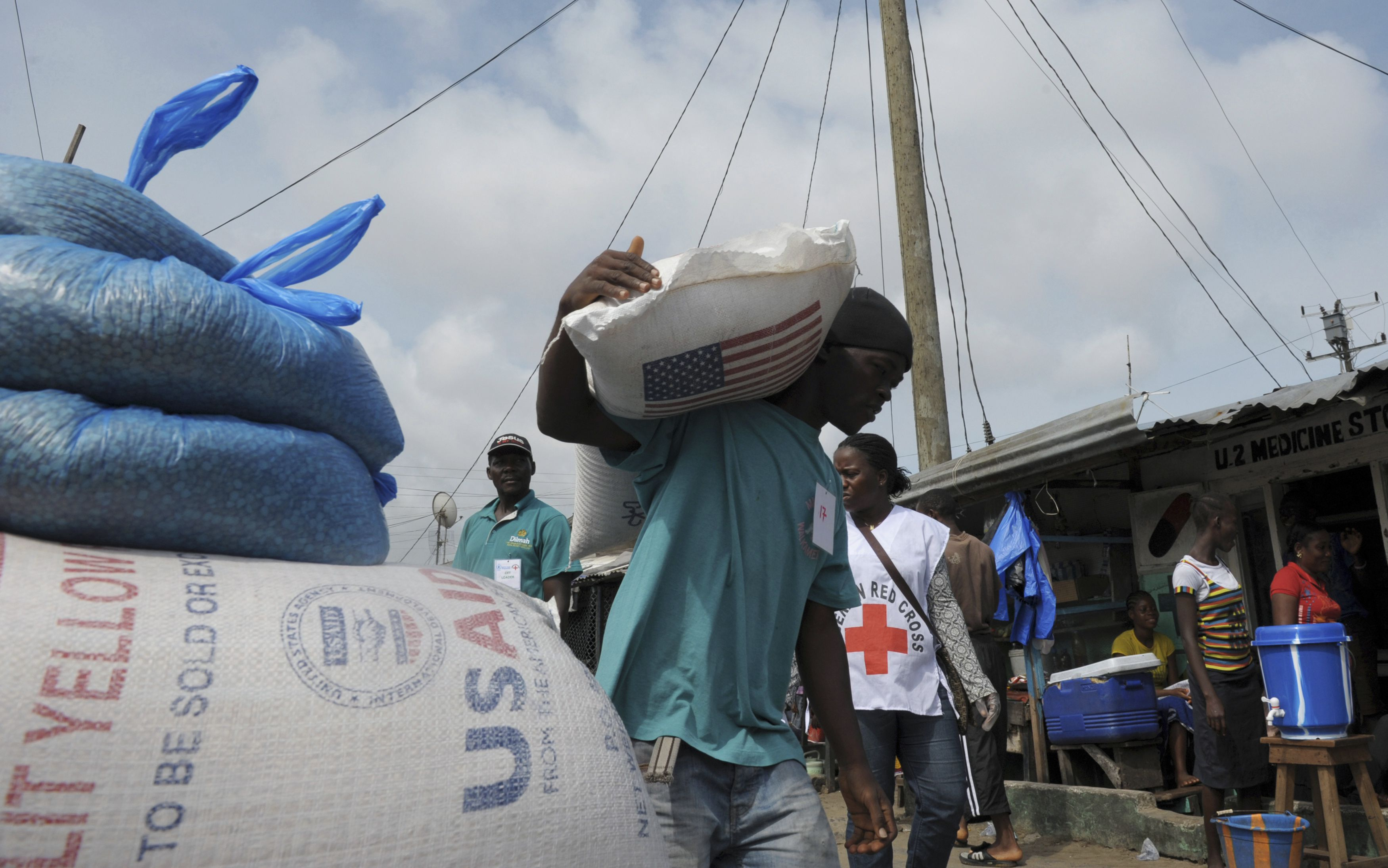 A resident of West Point neighbourhood, which has been quarantined following an outbreak of Ebola, carries a sack of food rations from the United Nations World Food Programme (WFP) in Monrovia August 28, 2014. Liberian authorities introduced a nationwide curfew last week and put the West Point neighbourhood under quarantine to curb the spread of the disease.             REUTERS/2Tango    (LIBERIA - Tags: HEALTH DISASTER SOCIETY) - RTR4469R