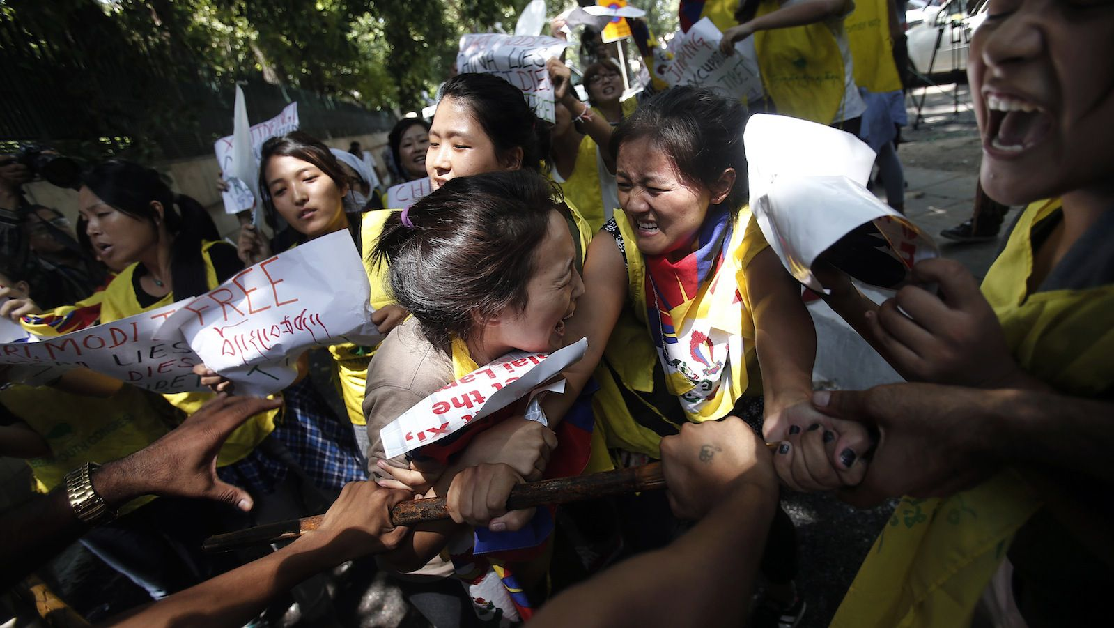 Tibetan exiles shout slogans as they scuffle with police during a protest outside the venue of a meeting between Chinese President Xi Jinping and Indian Prime Minister Narendra Modi in New Delhi September 18, 2014. Groups of Tibetan activists held noisy protests outside the hotel where Xi was staying in New Delhi, and at the stately Hyderabad House where he sat down for formal talks with Modi. REUTERS/Adnan Abidi (INDIA - Tags: CIVIL UNREST POLITICS) - RTR46PVW