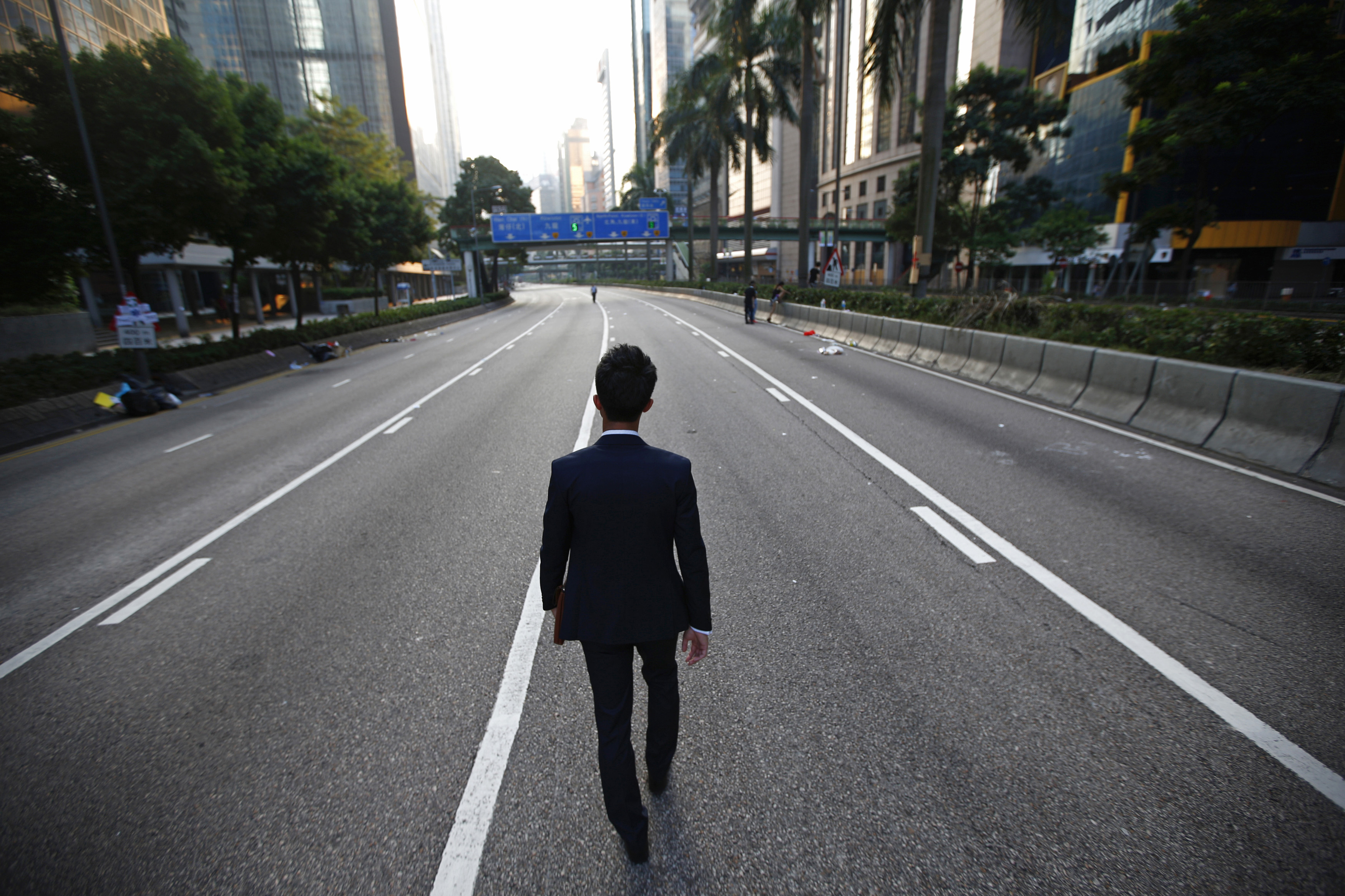 A man walks along an empty street near the central financial district in Hong Kong September 30, 2014. Tens of thousands of pro-democracy protesters extended a blockade of Hong Kong streets on Tuesday, stockpiling supplies and erecting makeshift barricades ahead of what some fear may be a push by police to clear the roads before Chinese National Day.   REUTERS/Carlos Barria (CHINA - Tags: POLITICS CIVIL UNREST) - RTR4891T