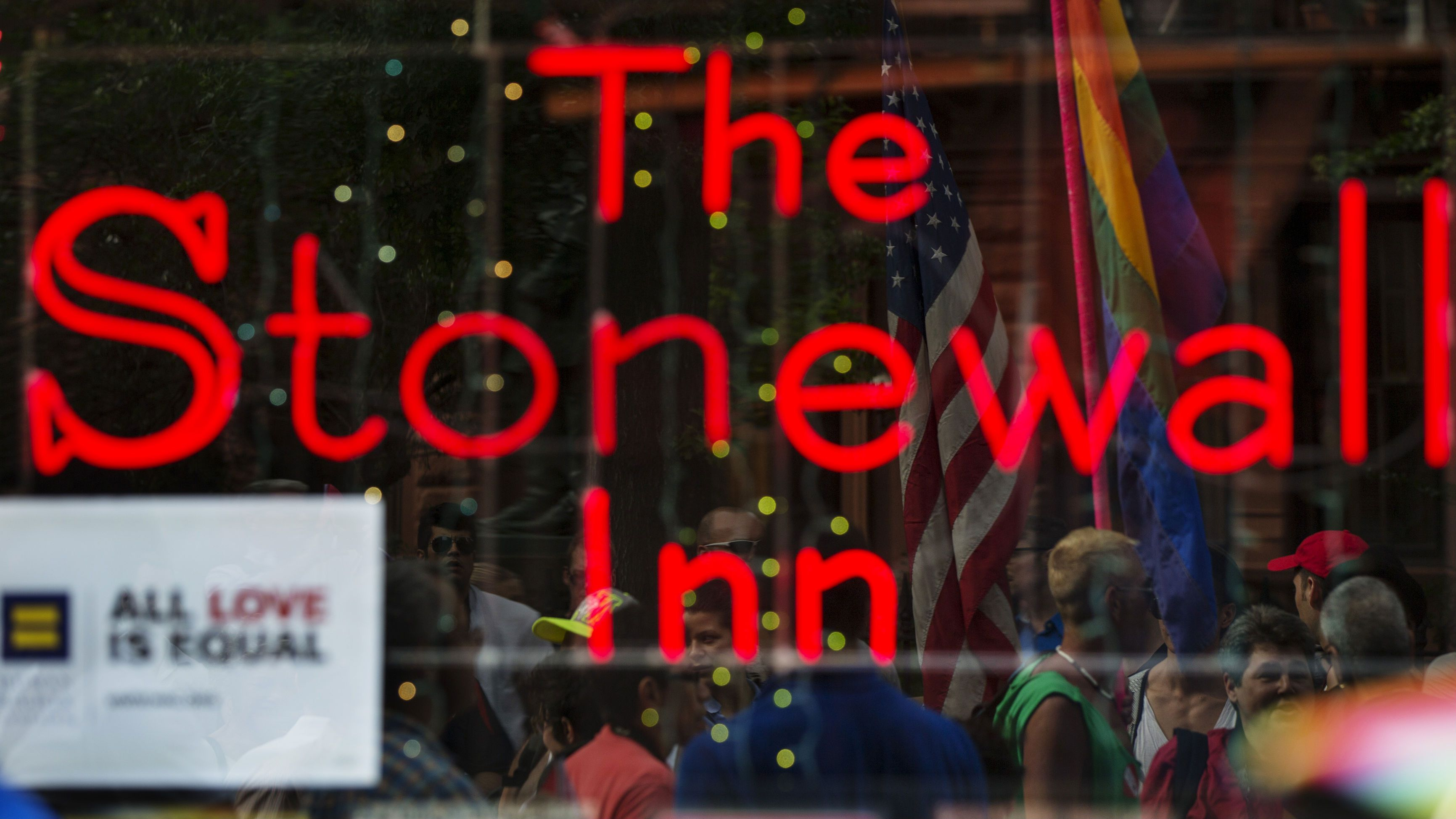 People celebrating the U.S. Supreme Court ruling against the Defense of Marriage Act can be seen reflected in the window of the Stonewall Inn in New York June 26, 2013. The U.S. Supreme Court delivered a landmark victory for gay rights on Wednesday by forcing the federal government to recognize same-sex marriages in states where it is legal and paving the way for it in California, the most populous state. REUTERS/Lucas Jackson (UNITED STATES - Tags: POLITICS SOCIETY)