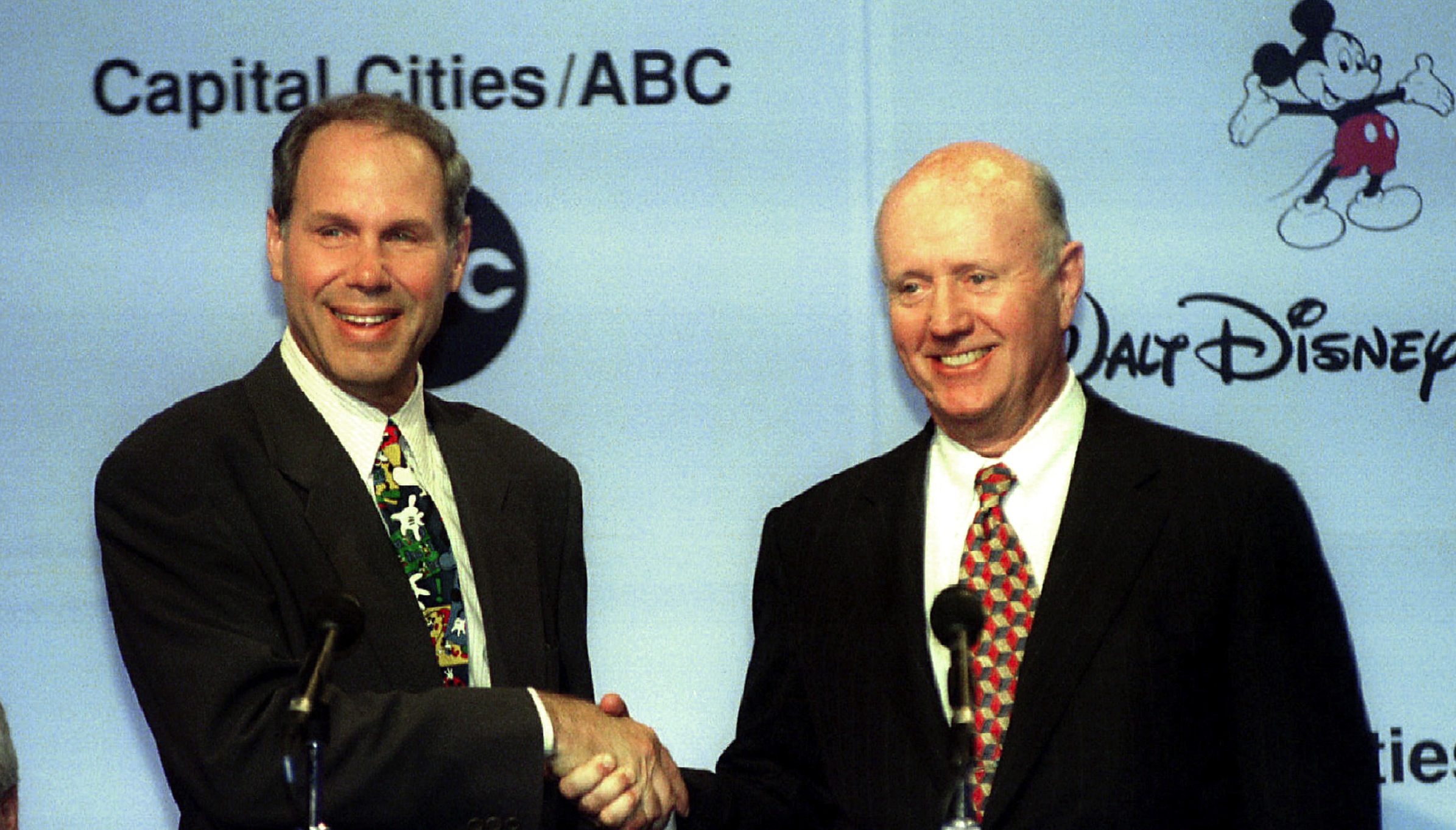 Walt Disney Company chairman Michael D. Eisner (L) shakes hands with Capital Cities/ABC chairman Thomas S. Murphy at a press conference in New York July 31 held to announce the merger of the two entertainment companies. Disney said it would pay $19 billion for Capital    Cities/ABC in a move that took [Hollywood and Wall Street] by surprise. - RTXFUFF