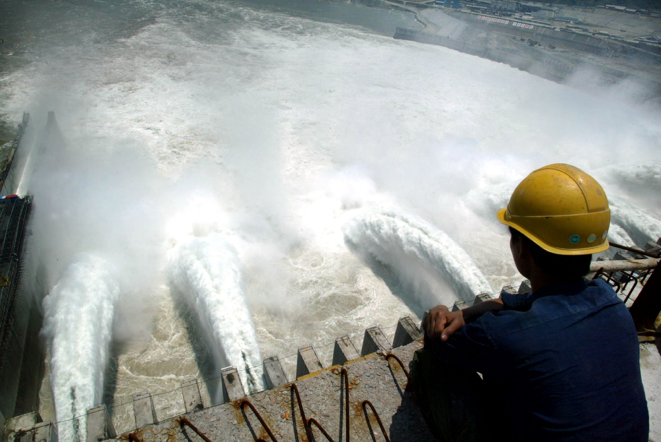 A Chinese worker looks at water gushing from open sluice gates on the main dam of the Three Gorges project in Yichang, Hubei Province, June 11, 2003. China successfully filled the water level up to 135 metres at a 600-metre-long reservoir for the world's biggest hydroelectric project after blocking the massive Yangtze River