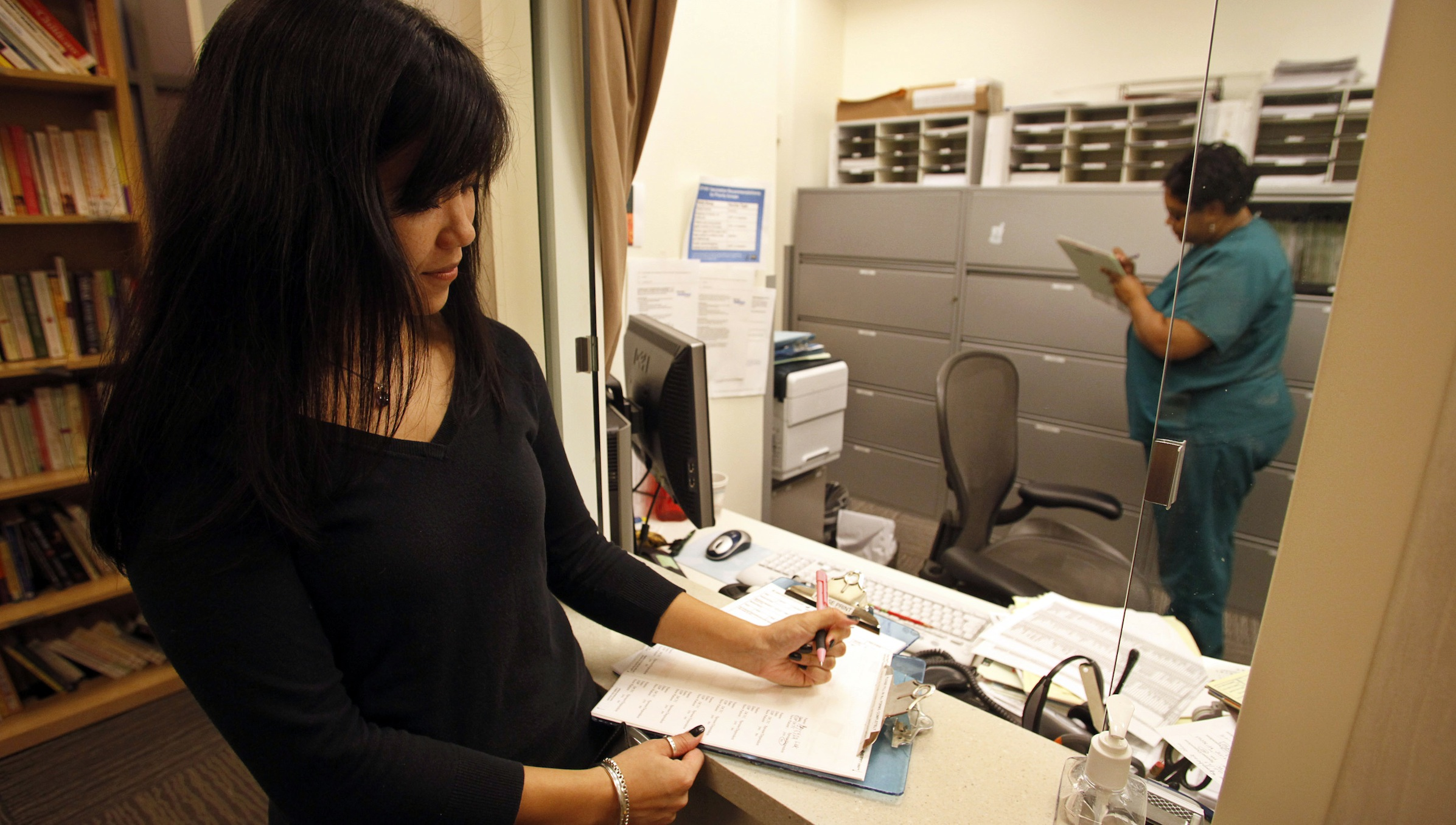 Bonnary Lek, a manager at Discovery Communications headquarters, signs in for a medical appointment at the Discovery Wellness Center at the company's headquarters in Silver Spring, Maryland December 3, 2009. The parent of Animal Planet, the Discovery Channel and other major cable television channels calculates it saved $5 million since opening a corporate wellness center with a clinic and other wellness programs five years ago. About $4 million of that is from lower medical claim costs. Picture taken December 3, 2009. As Democratic lawmakers in Washington inch ahead with plans to overhaul the U.S. healthcare system, companies like Discovery are striking out on their own -- whether through on-site doctors or diet plans -- to rein in soaring costs in a nation where employers still pay for the bulk of medical care. To match Special Report USA-HEALTHCARE/WELLNESS   REUTERS/Jim Bourg   (UNITED STATES HEALTH BUSINESS SOCIETY) - RTXRMUO