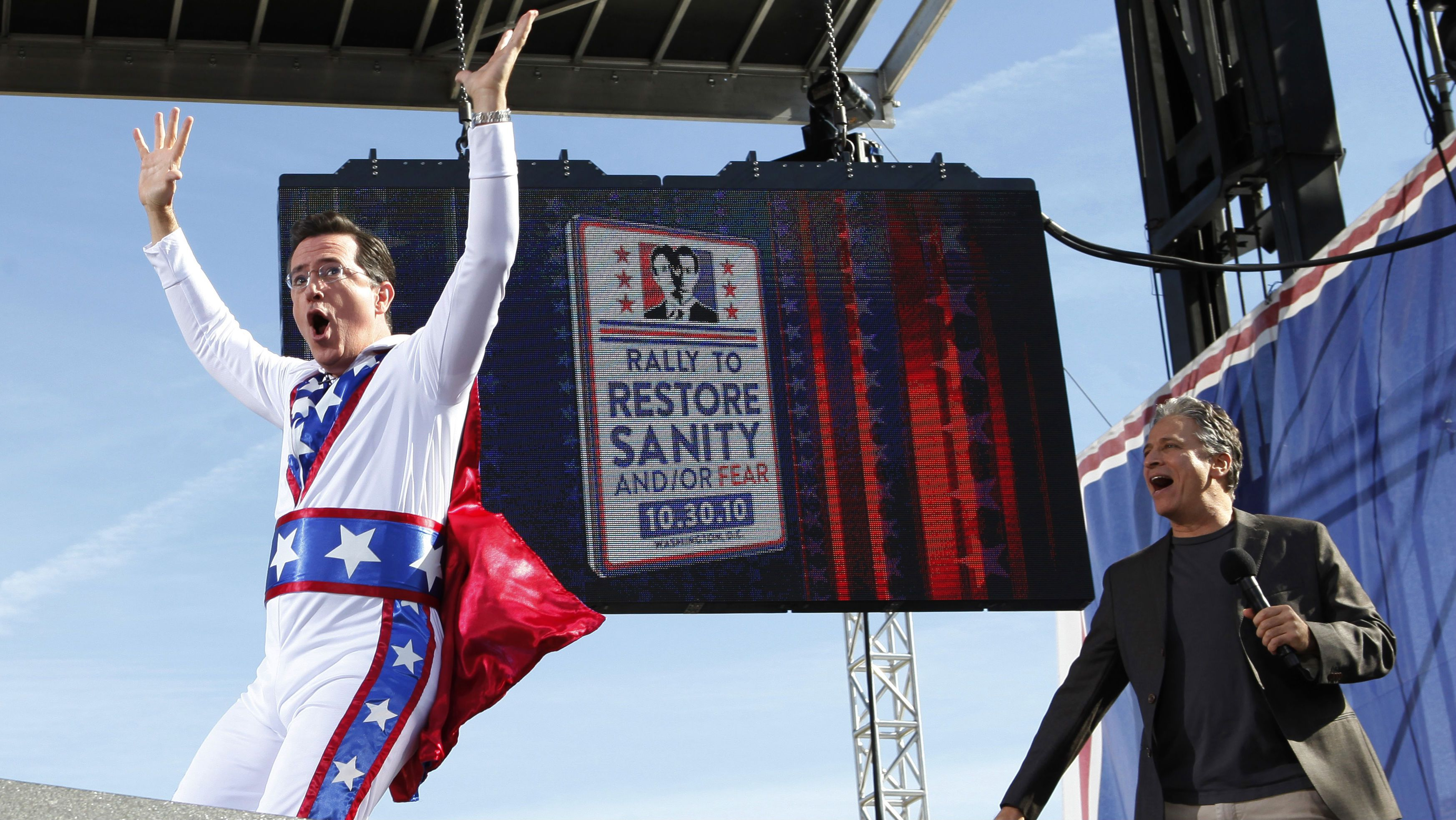 """Comedian Stephen Colbert (L) runs across the stage in front of fellow rally host Jon Stewart during their """"Rally to Restore Sanity and/or Fear"""" on the National Mall in Washington October 30, 2010. The rally is a counterpoint to recent partisan political rallies on both ends of the U.S. political spectrum held in anticipation of the November 2nd Congressional midterm elections. REUTERS/Jim Bourg (UNITED STATES - Tags: POLITICS ENTERTAINMENT SOCIETY CIVIL UNREST)"""