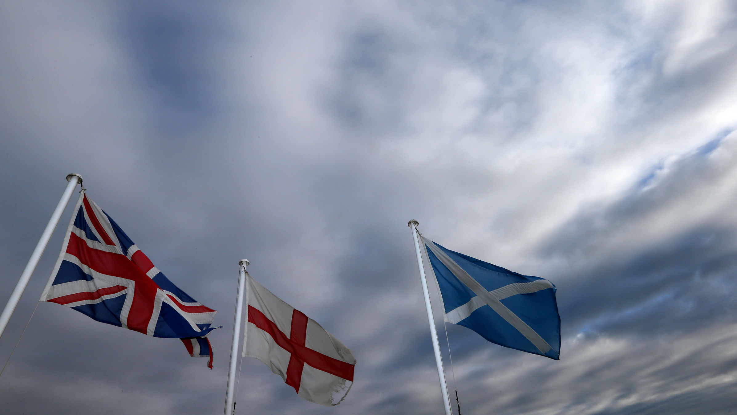 From left, the Union Jack, St George's Cross and the Saltire fly at Adderstone, England, Monday, Sept. 8, 2014. The British government plans to offer Scotland more financial autonomy in the coming days as polls predict a very close vote in the September 18 on Scottish independence. (AP Photo/Scott Heppell)