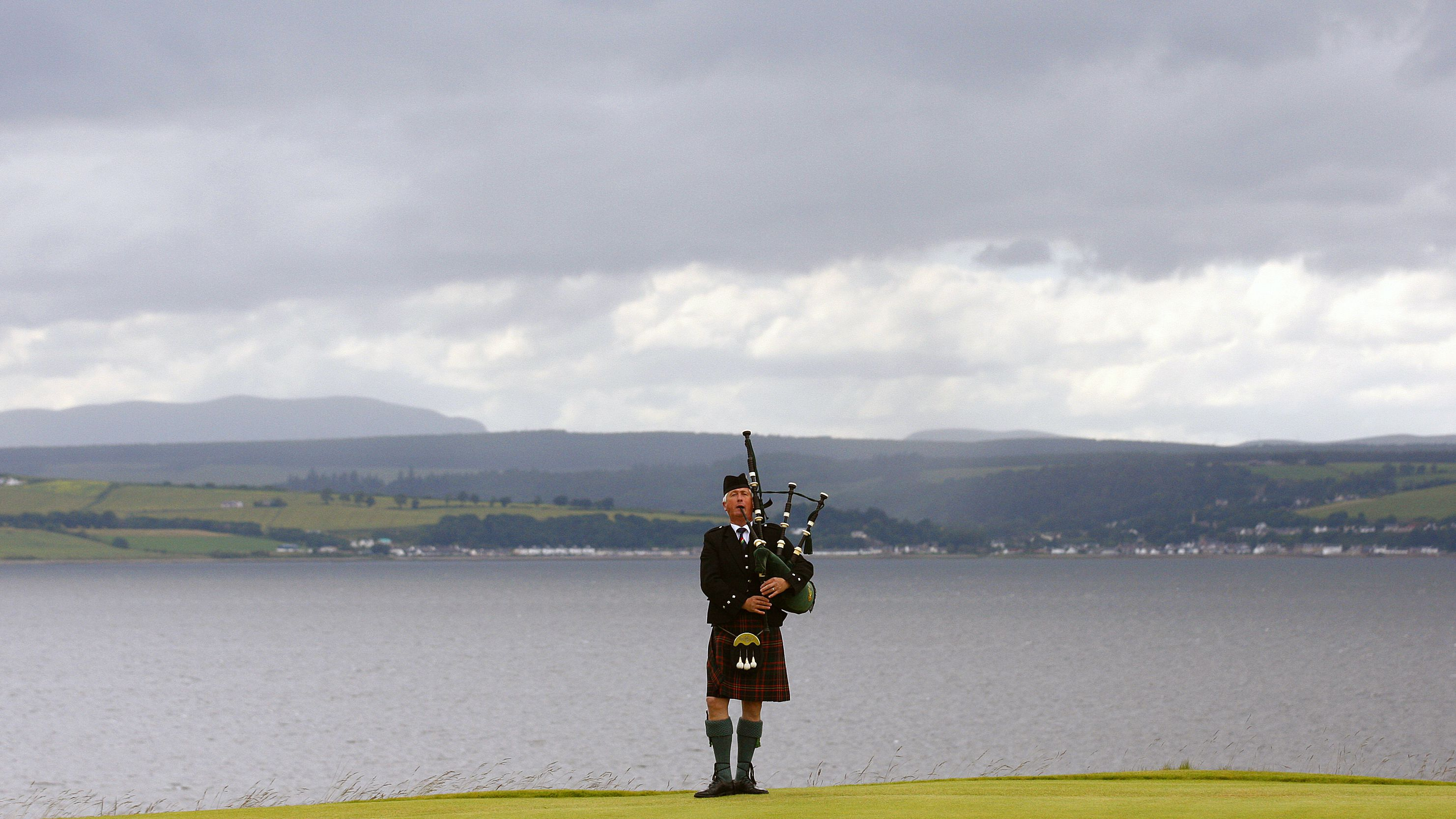 A bagpiper plays on the 18th green before the winner's presentation ceremony of the Scottish Open golf tournament at Castle Stuart golf course near Inverness, Scotland July 15, 2012. REUTERS/David Moir (BRITAIN - Tags: SPORT GOLF TPX IMAGES OF THE DAY)