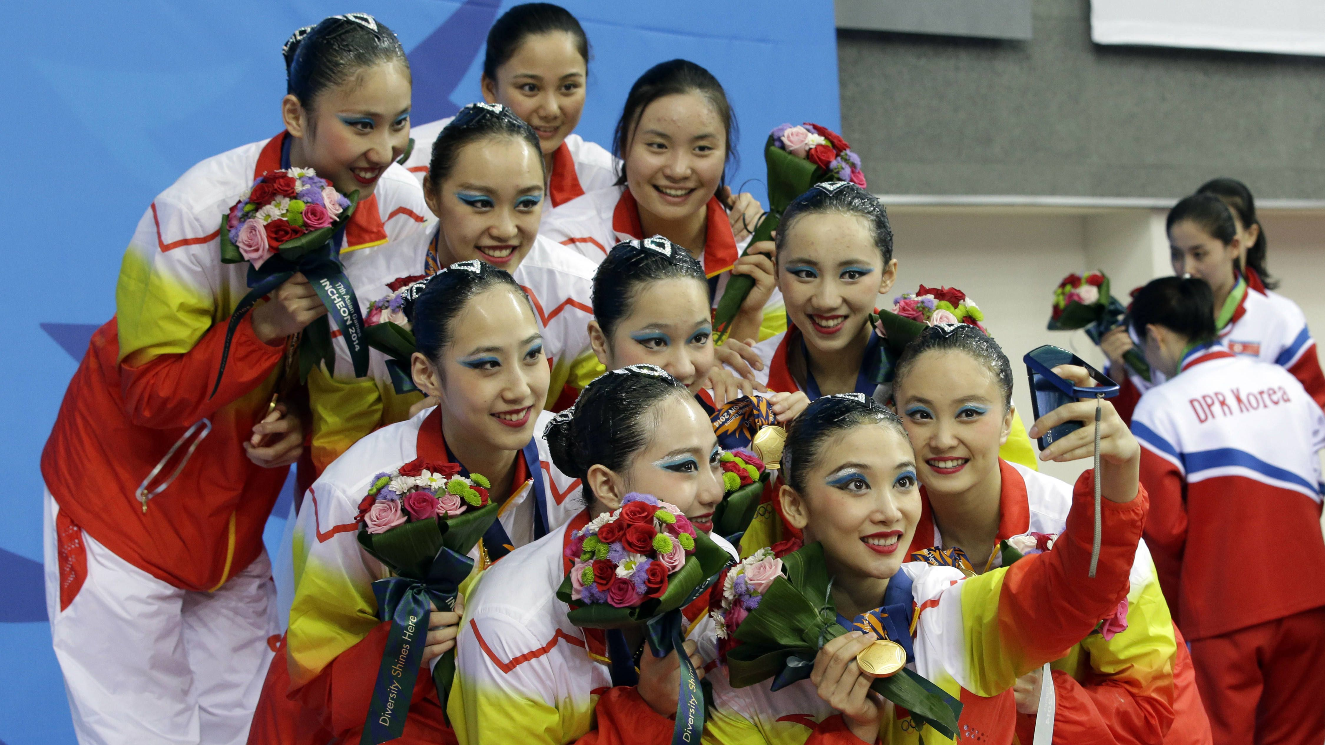 Chinese synchronized swimming team members take selfie with their gold medals after their synchronized swimming team free routine at the 17th Asian Games in Incheon, South Korea, Monday, Sept. 22, 2014. (AP Photo/Lee Jin-man)