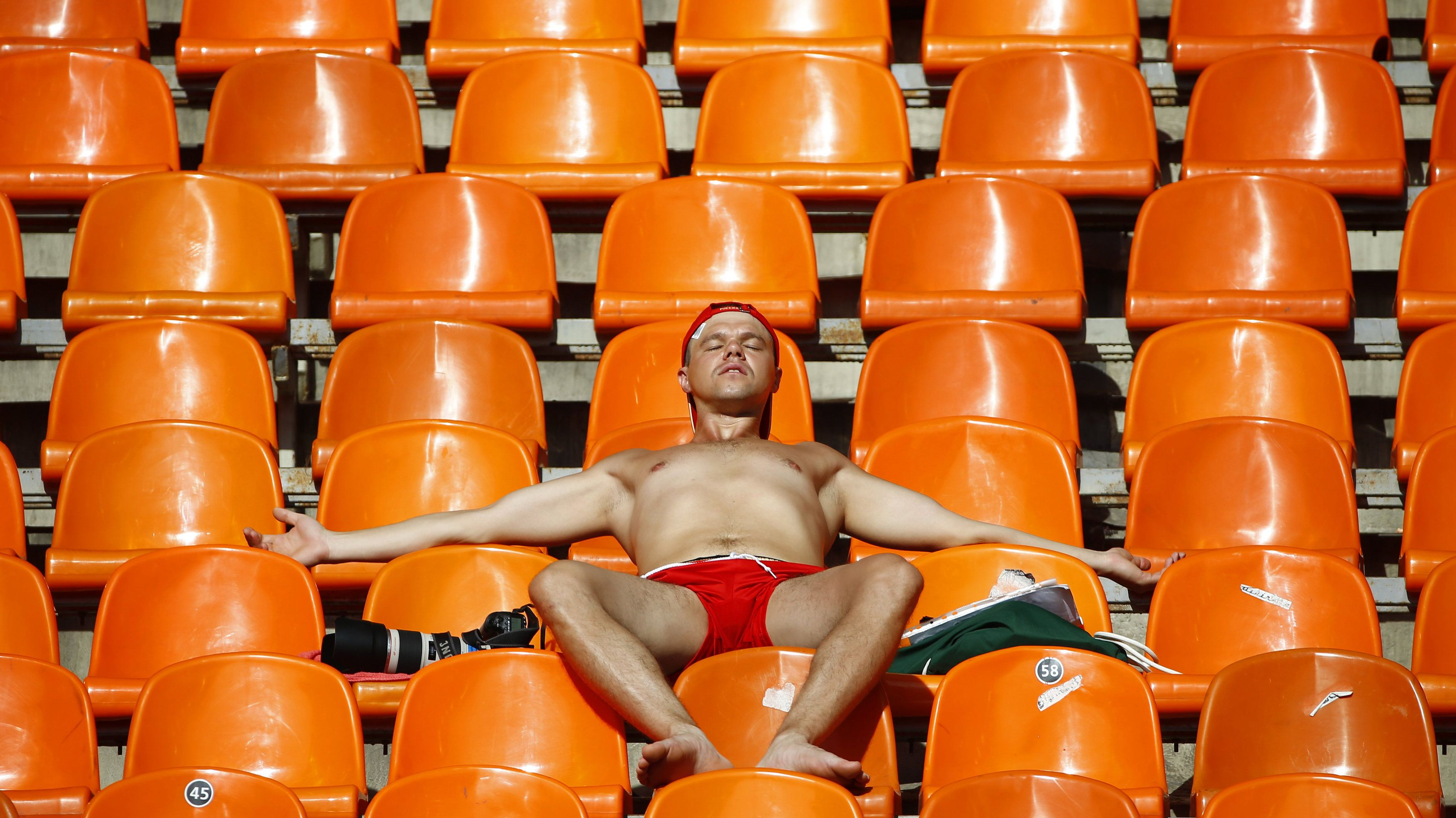 A spectator tans himself in the sun during the morning session of the IAAF World Athletics Championships at the Luzhniki stadium in Moscow August 13, 2013. REUTERS/Kai Pfaffenbach