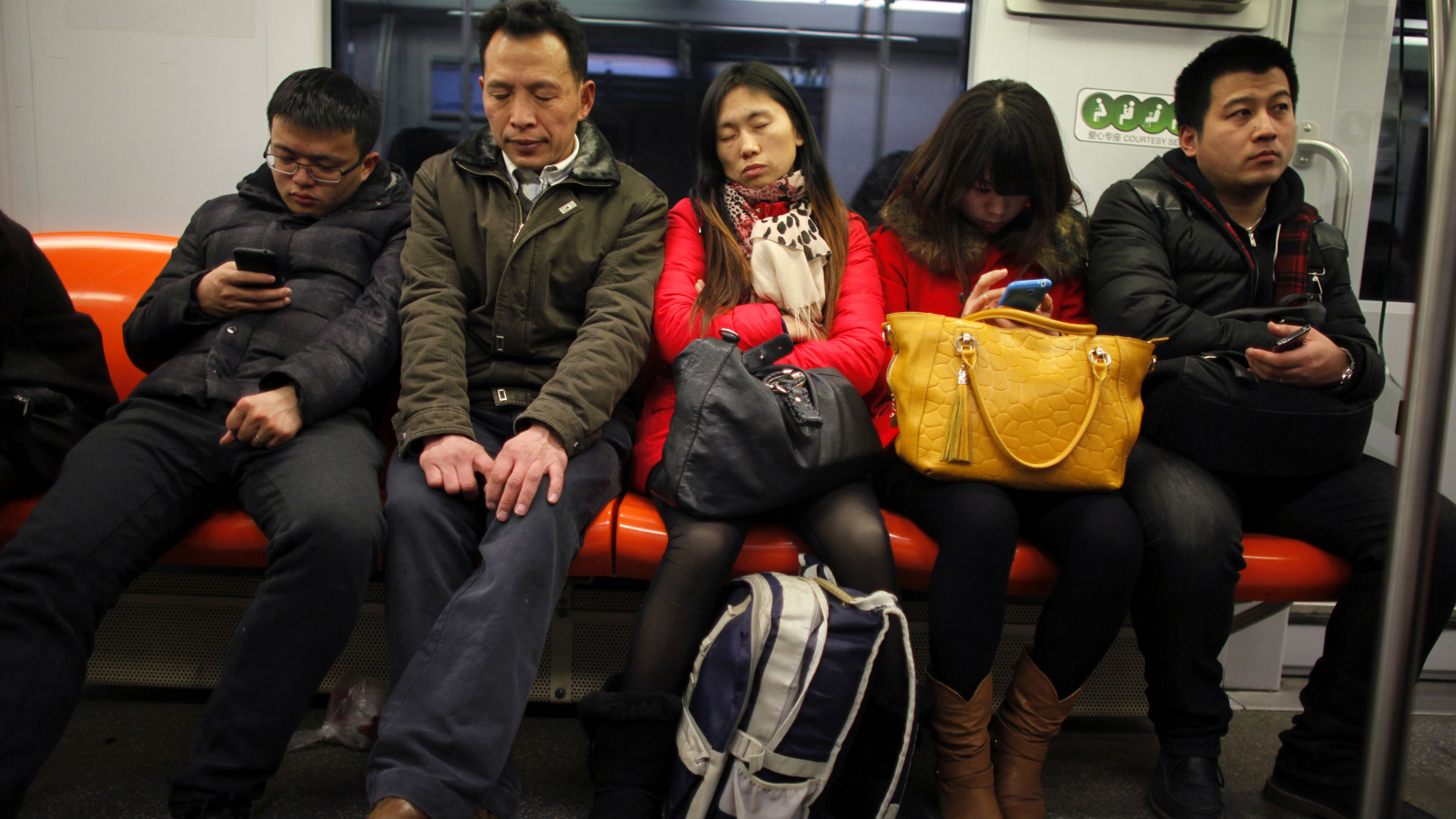 Shi Huaju (C) sleeps while riding the subway at the start of her annual trip for Spring Festival in Shanghai January 27, 2013. Like millions of migrant workers, Shi and her husband Li Anhua make the long trek home for the Chinese Spring Festival, travelling for 50 hours by train and bus during peak season to see their two children in Sichuan province after a long year of separation. Public transportation authorities expect about 3.41 billion train, flight and bus journeys to take place nationwide over the week-long Chinese New Year holiday. Picture taken January 27, 2013.