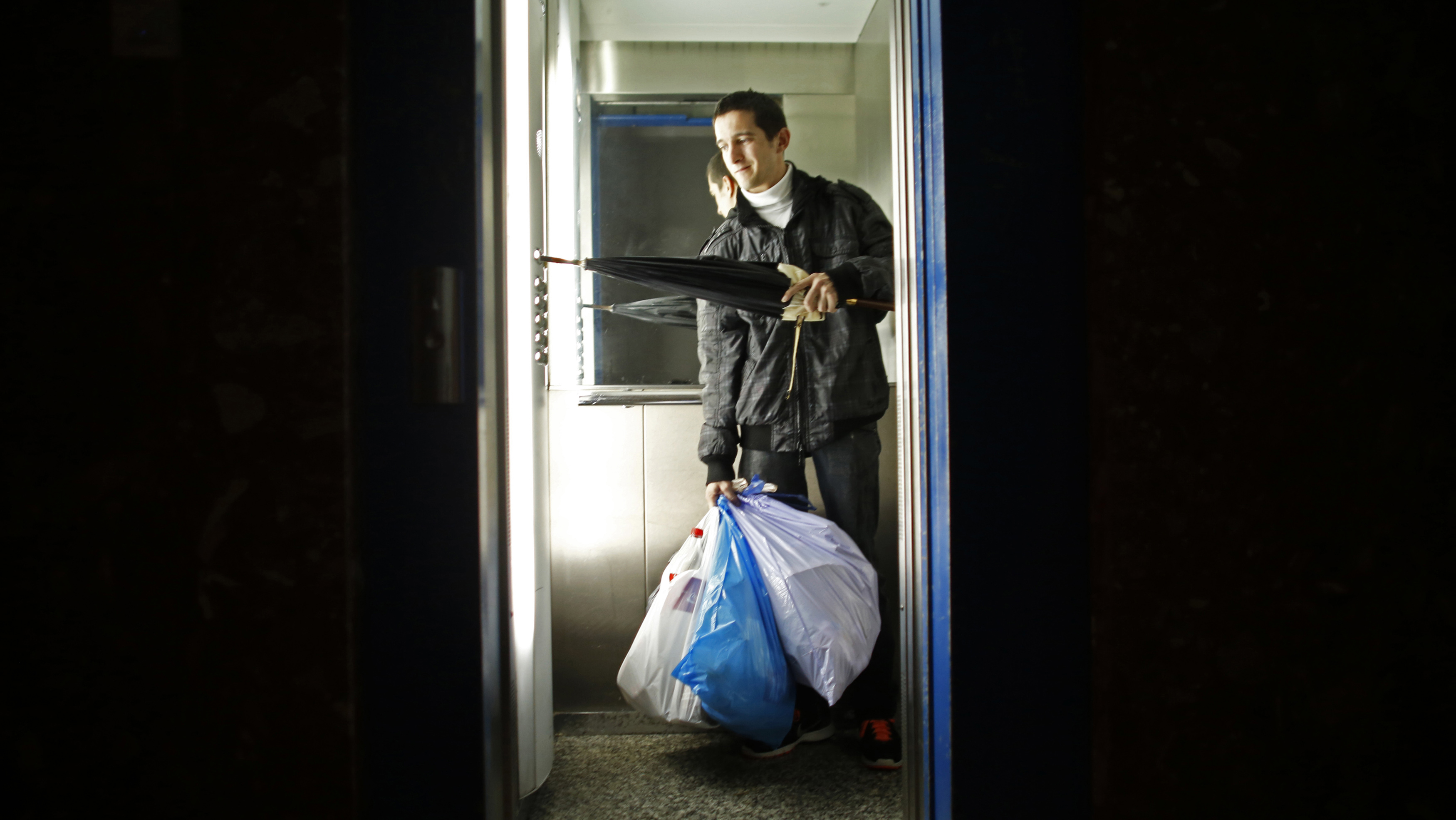 Jesus Pardal, an unemployed 29-year-old father-to-be, pushes buttons in an elevator holding garbage bags containing other people's trash to take out to earn 0.50 euro cents (0.60 US cents) in Cadiz, southern Spain November 2, 2012. Spain's number of jobless rose by 2.7 percent in October from a month earlier, or by 128,242 people, leaving 4.8 million people out of work, data from the Labour Ministry showed on Monday. This was the third straight month the jobless figures rose after a respite during the summer tourism season. Picture taken November 2, 2012. REUTERS/Marcelo del Pozo (SPAIN - Tags: BUSINESS EMPLOYMENT SOCIETY POVERTY TPX IMAGES OF THE DAY)