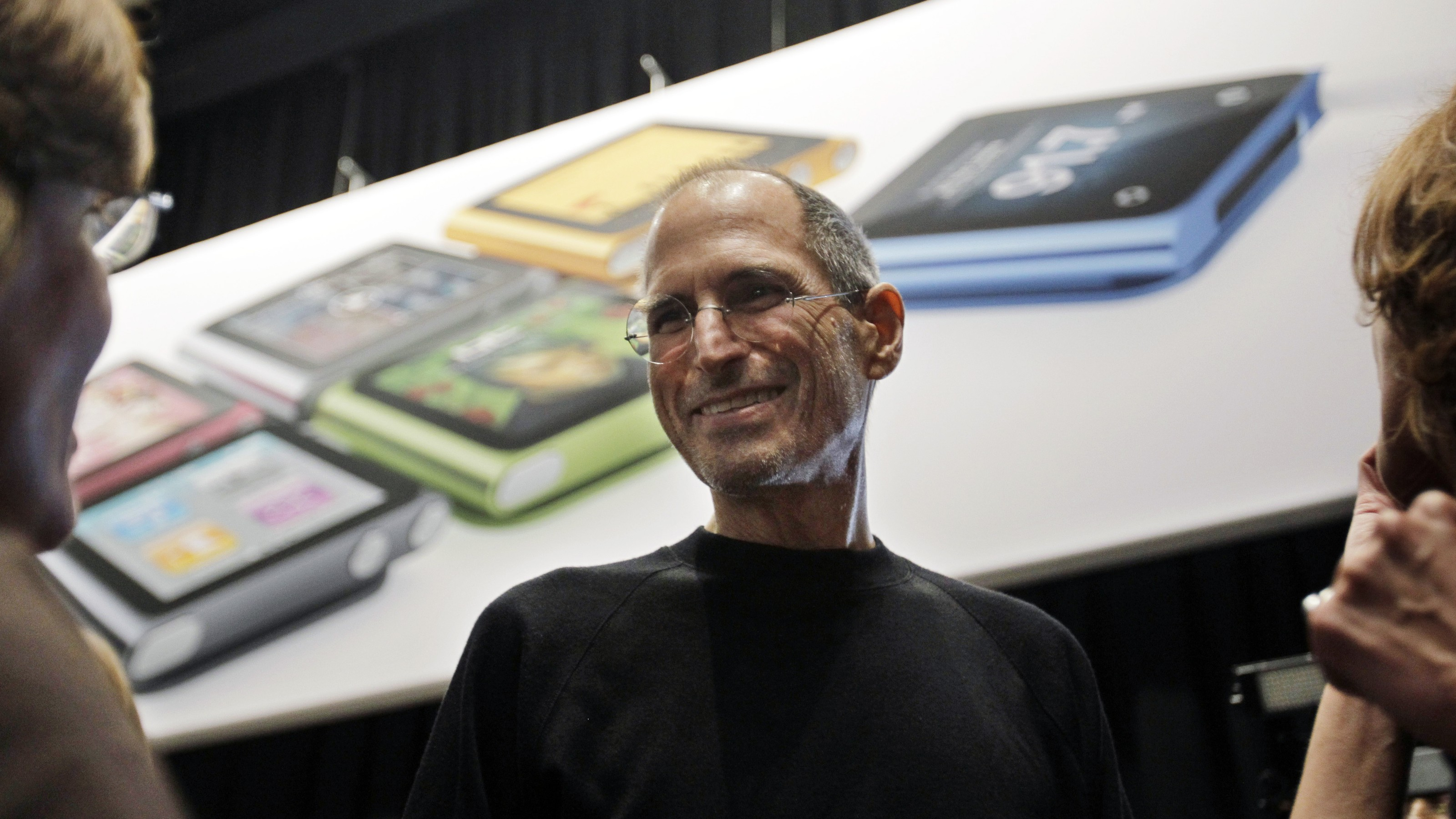 Apple CEO Steve Jobs smiles in front of an iPod Shuffle poster, Wednesday, Sept. 1, 2010, in San Francisco. (AP Photo/Paul Sakuma)