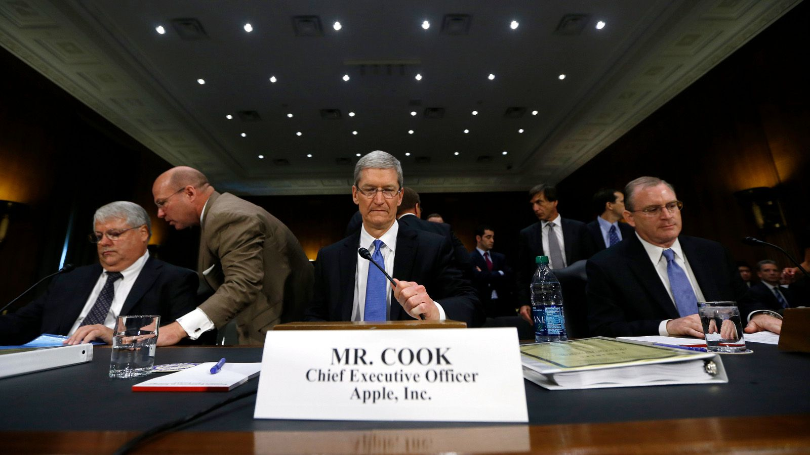 Apple CEO Tim Cook (C), CFO Peter Oppenheimer (L) and Apple Head of tax operations Philip Bullock appear before a Senate homeland security and governmental affairs investigations subcommittee hearing on offshore profit shifting and the U.S. tax code, on Capitol Hill in Washington, May 21, 2013. Apple Inc came under fire on Tuesday at a Senate hearing over an investigation that alleged the U.S. high technology icon has kept billions of dollars in profits in Irish subsidiaries and paid little or no taxes to any government.