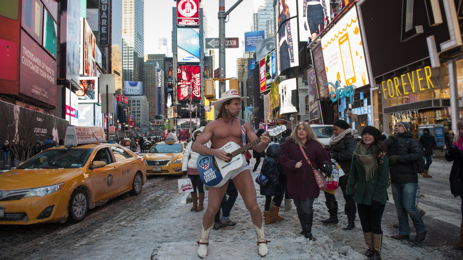 Robert Burck (L), also known as the original 'Naked Cowboy', performs after snowfall on the streets of Times Square, New York January 3, 2014. A heavy snowfall and dangerously low temperatures gripped the northeastern United States on Friday, grounding flights, closing schools and government offices across the region and causing at least three deaths. Burck, who started performing in Times Square in 1998, claims to make up to $150,000 a year in tips alone.