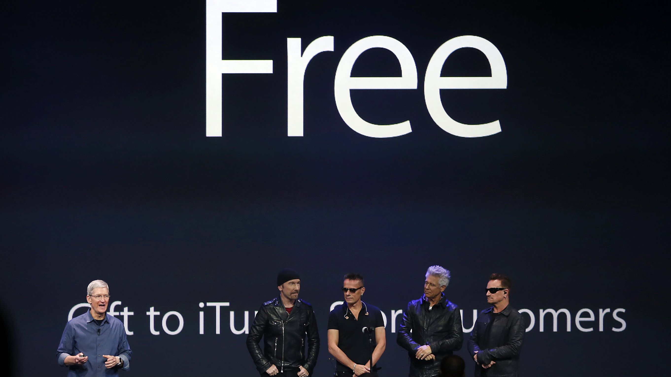 Apple CEO Tim Cook (L) stands with Irish rock band U2 as he speaks during an Apple event announcing the iPhone 6 and the Apple Watch at the Flint Center in Cupertino, California, September 9, 2014.
