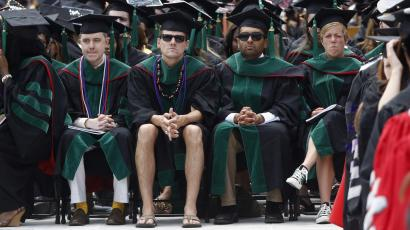 A student in flip flops and shorts (C) watches as U.S. President Barack Obama (not pictured) receives an honorary degree during the spring commencement ceremony at Ohio State University in Columbus, May 5, 2013. REUTERS/Jason Reed (UNITED STATES - Tags: POLITICS EDUCATION SOCIETY TPX IMAGES OF THE DAY)