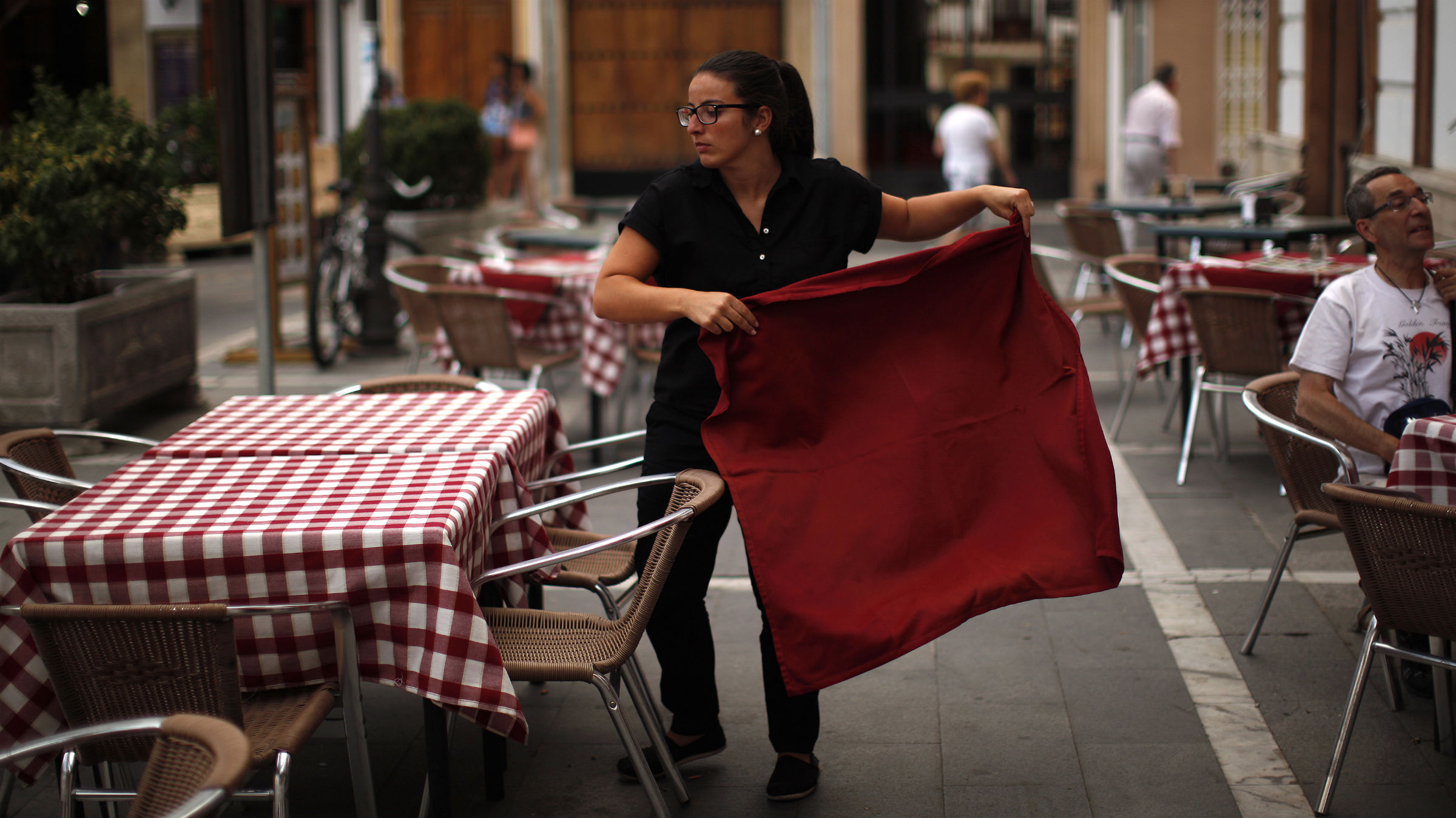 "Marina Alcantara, 29, an unemployed English teacher who has been hired as a temporary waitress since last July 24, arranges a tablecloth at the terrace of the ""Casino de Ronda"" restaurant in downtown Ronda restaurant in downtown Ronda, near Malaga, southern Spain July 24, 2014. Spain's unemployment rate fell to its lowest level in two years in the second quarter, data showed on Thursday, lifted by strong job creation in the services sector and adding to hopes of a sustained economic turnaround. Unemployment fell to 24.5 percent from 25.9 percent a quarter earlier, the National Statistics Institute said."