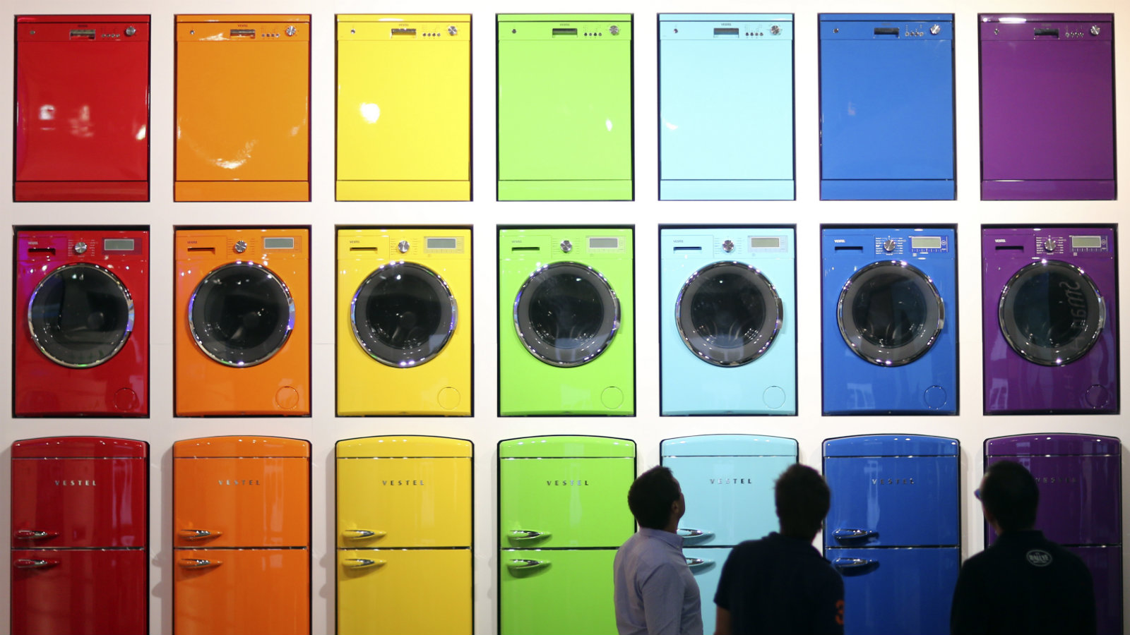 Visitors look at a display of stoves, dishwashers, washing machines and integrated fridge freezers (from top to bottom) produced by Vestel during the IFA Electronics show in Berlin September 4, 2014. REUTERS/Hannibal Hanschke (GERMANY - Tags: BUSINESS SCIENCE TECHNOLOGY)