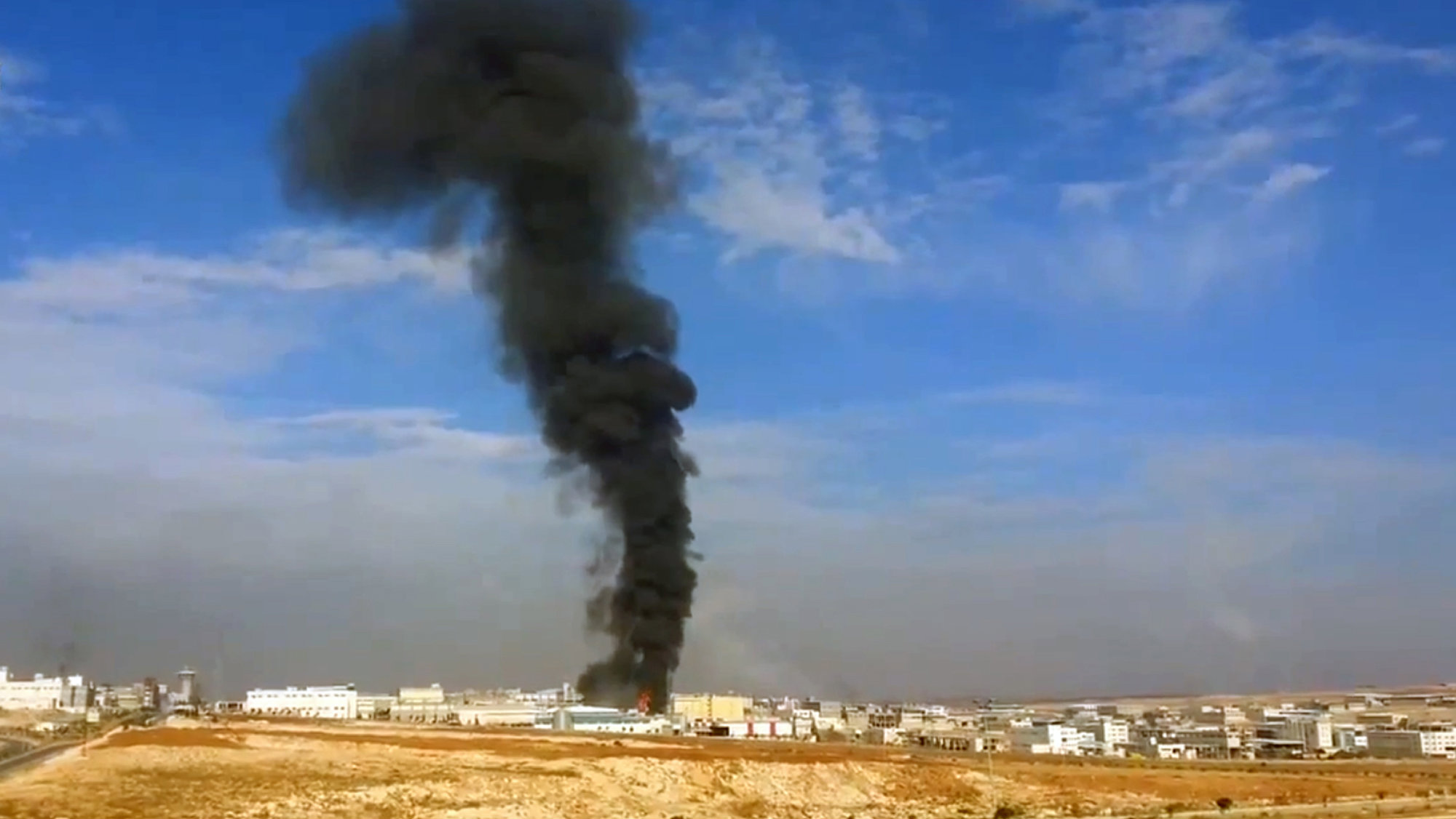 In this image taken from a Saturday, Nov. 23, 2013, video obtained from the Sham News Network and is consistent with independent AP reporting, smoke billows from the Aleppo Industrial City as a result of heavy shelling near Aleppo, Syria. A string of government airstrikes on rebel-held areas in northern Syria killed scores of people Saturday, activists said, as al-Qaida-linked rebels captured one of the country's major oil fields in the east.