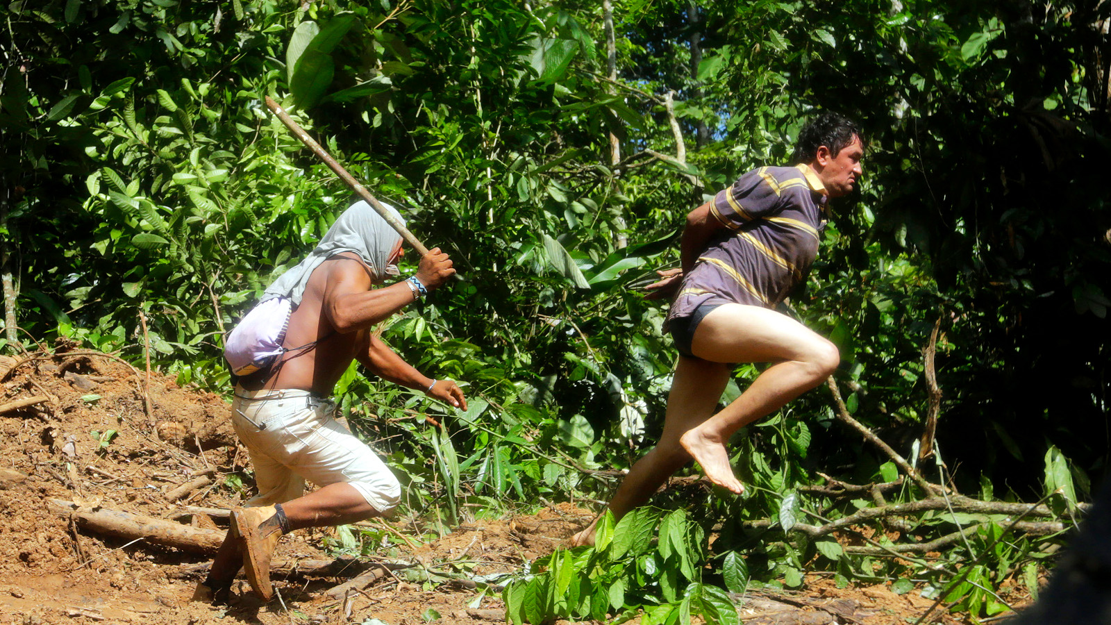 A Ka'apor Indian warrior (L) chases a logger who tried to escape after he was captured during a jungle expedition to search for and expel loggers from the Alto Turiacu Indian territory, near the Centro do Guilherme municipality in the northeast of Maranhao state in the Amazon basin, August 7, 2014. Tired of what they say is a lack of sufficient government assistance in keeping loggers off their land, the Ka'apor Indians, who along with four other tribes are the legal inhabitants and caretakers of the territory, have sent their warriors out to expel all loggers they find and set up monitoring camps in the areas that are being illegally exploited. Picture taken August 7, 2014.