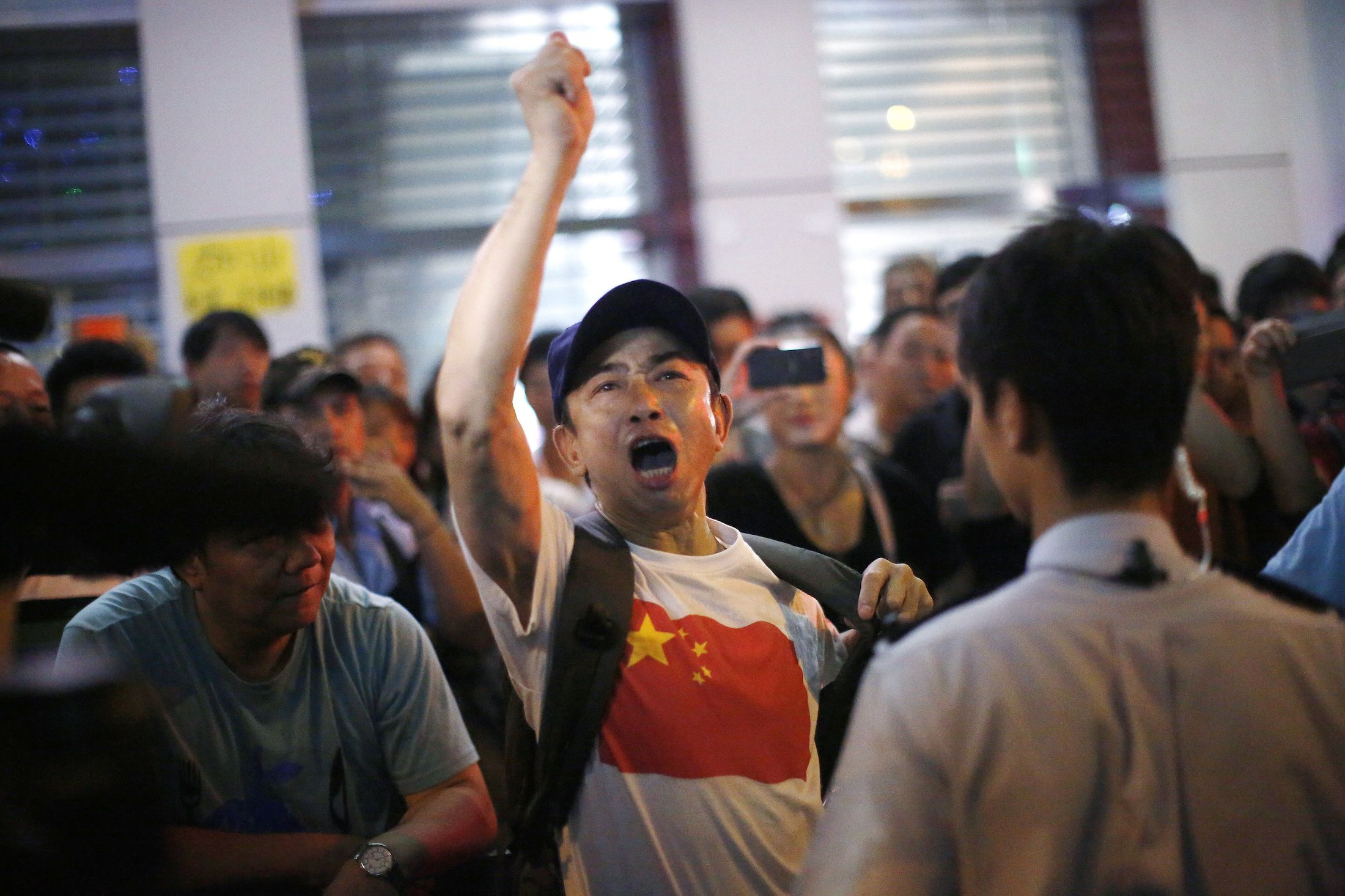 An anti-Occupy Central protester argues with pro-democracy protesters on a main street at Hong Kong