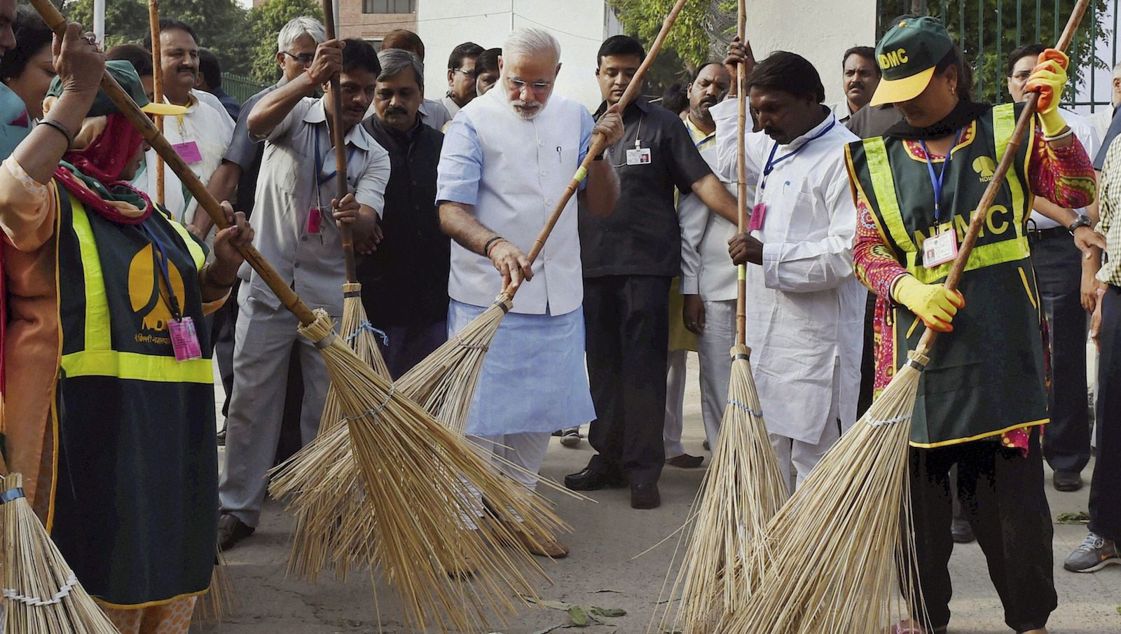 Indian Prime Minister Narendra Modi, center, sweeps an a road with a broom along with civic workers in New Delhi, India, Thursday, Oct. 2, 2014. Modi joined millions of schoolchildren, officials and ordinary people who picked up brooms and dustpans Thursday in a countrywide campaign to clean parks, public buildings and streets. (AP Photo/Press Trust of India)