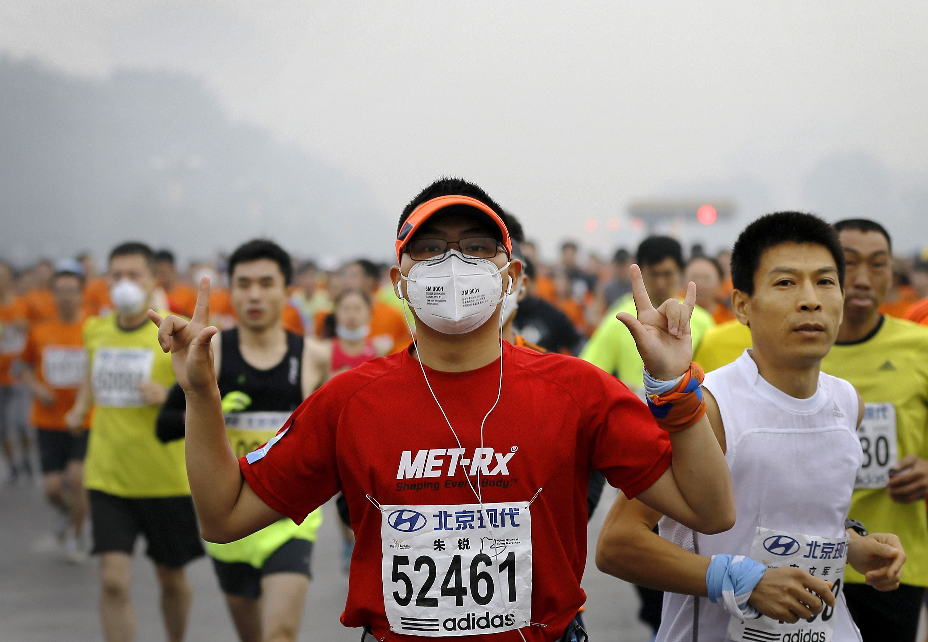 A runner wearing a mask to protect himself from pollutants gestures as he and others jog past Chang'an Avenue near Tiananmen Square shrouded in haze at the start of 2014 Beijing International Marathon in Beijing, China Sunday, Oct. 19, 2014. (AP Photo/Andy Wong)