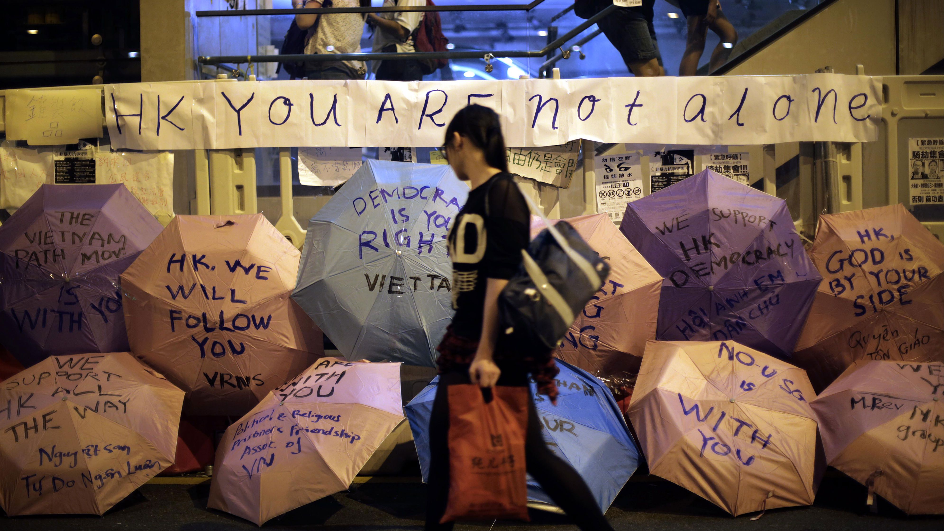 A student protester walks past umbrellas with words of support written on them at the pro-democracy protest site near government headquarters, Saturday, Oct. 4, 2014 in Hong Kong. Early Saturday, the Hong Kong Federation of Students, one of the groups leading the demonstrations that drew tens of thousands of people earlier this week, said they saw no choice but to cancel the dialogue they had agreed to after Hong Kong's Chief Executive Leung Chun-ying's proposed talks. They demanded the government hold someone responsible for the scuffles Friday, the worst disturbances since police used tear gas and pepper spray to try to disperse the protesters the weekend before. (AP Photo/Wong Maye-E)
