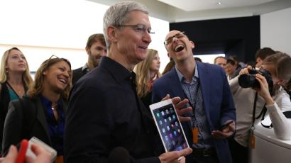 Apple CEO Tim Cook holds an iPad after a presentation at Apple headquarters in Cupertino, California October 16, 2014. REUTERS/Robert Galbraith