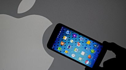 Samsung Galaxy S5 smartphone is held next to a logo of Apple in this September 23, 2014 illustration photo in Sarajevo. REUTERS/Dado Ruvic (BOSNIA AND HERZEGOVINA - Tags: BUSINESS TELECOMS)