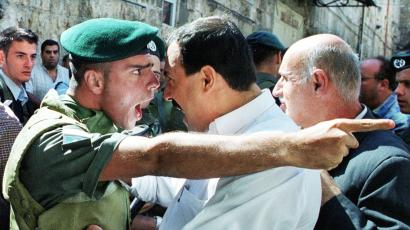 An Israeli Border Policeman and a Palestinian scream at each other face to face in the Old City of Jerusalem October 13, 2000 as the Palestinian is refused entry to the al-Aqsa mosque for Friday prayers. Israeli security forces prevented thousands of Palestinians from attending Friday prayers over concern for continued unrest and clashes following the prayers due to the increased tensions and fighting in the West Bank and Gaza Strip. REUTERS/Amit Shabi