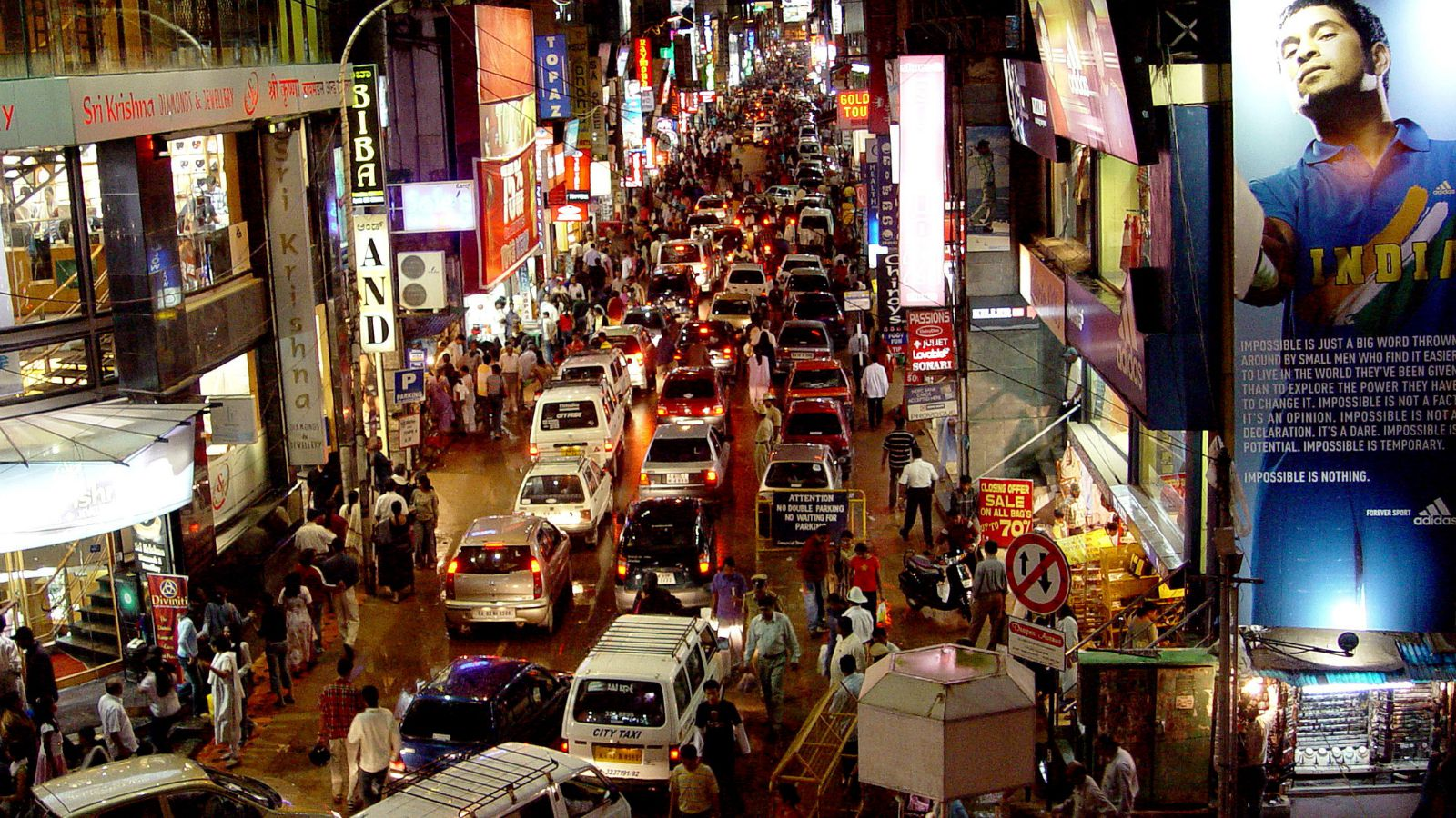 "Commuters are seen on a busy commercial street in the southern Indian city of Bangalore in this photo taken on October 2, 2004. [When narrow colonial-era streets get jammed with evening traffic in India's technology capital, the radio disc jockey on car stereos turns agony aunt. ""I want you to vent all your frustrations by screaming as hard as you want to,"" Darius Sunawala tells a rush-hour commuter moaning by phone about potholed roads in Bangalore."