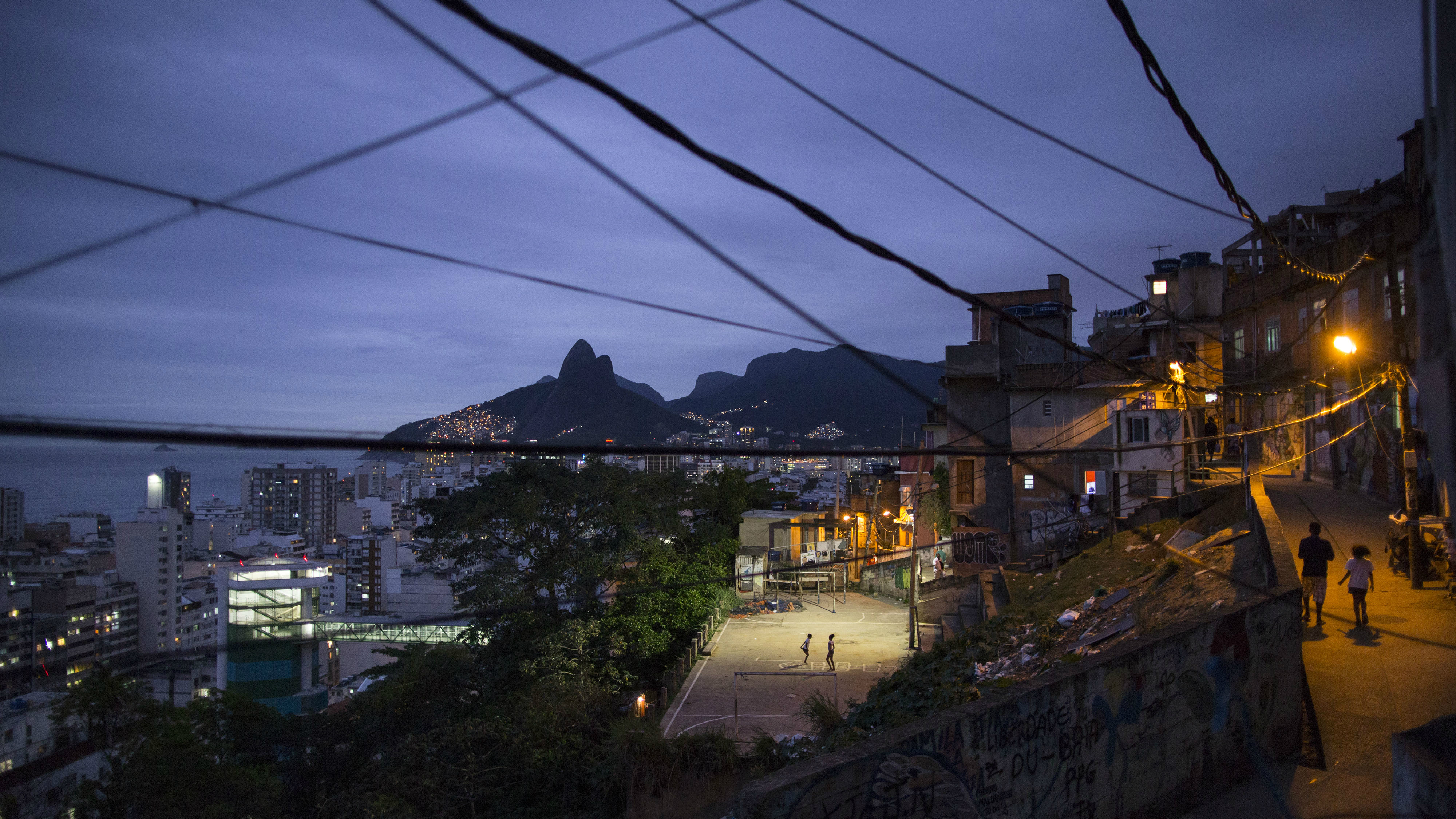 In this Oct. 21, 2014 photo, the upscale Ipanema neighborhood, left, stands along the coast, seen from the Cantagalo slum in Rio de Janeiro, Brazil. Polls have shown the poor overwhelmingly support President Dilma Rousseff, who is running for reelection, while the rich are massively behind opposition candidate Aecio Neves ahead of the Oct. 26 presidential run-off election. (AP Photo/Felipe Dana)