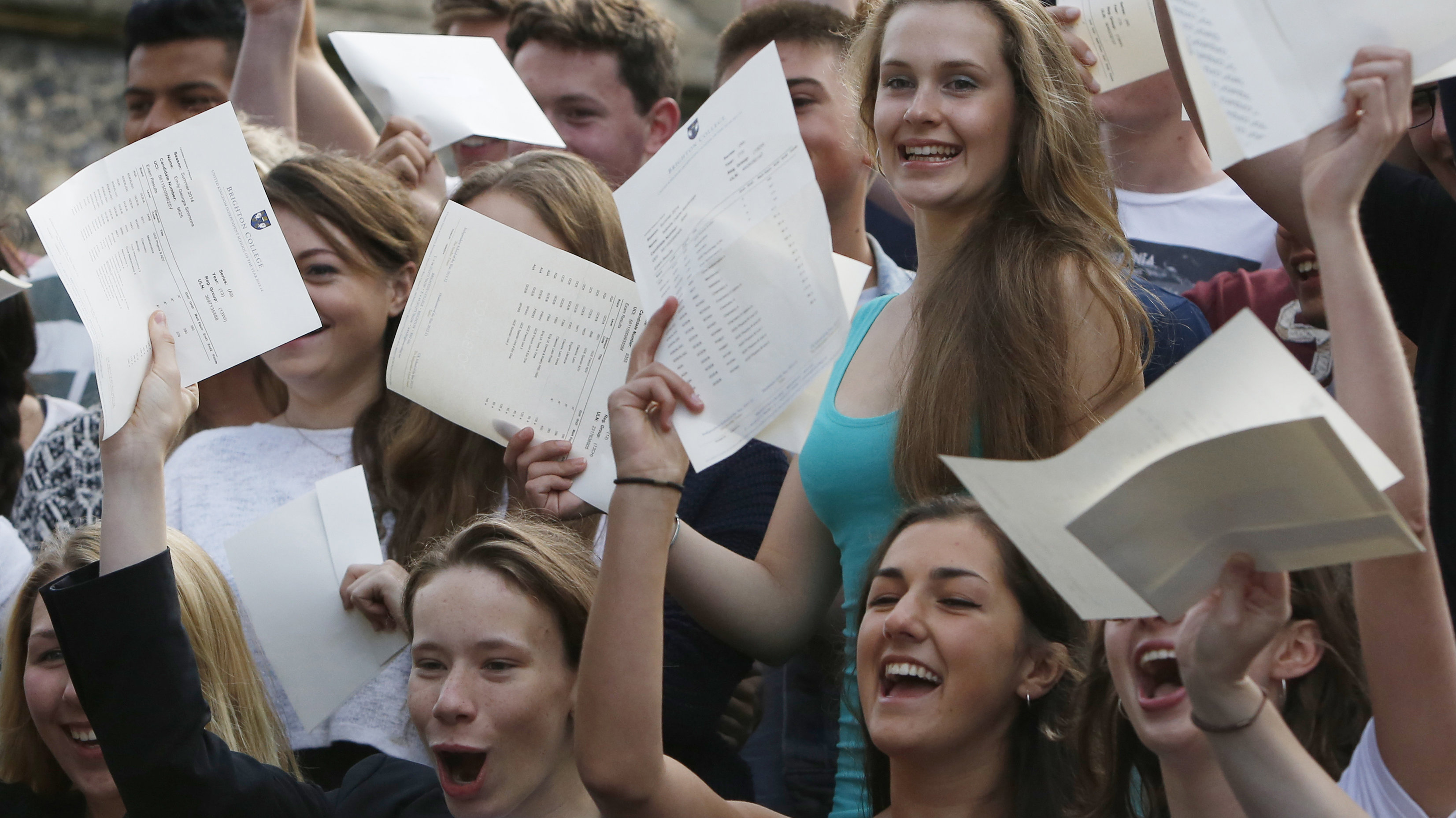 A-level student Tabitha Jackson (top R) poses with classmates for photographs, after she received her results of 4 A* A-levels, with a passrate of 99% dropping only 14 points out of a possible 1600, at Brighton College in Brighton, southern England August 14, 2014. Hundreds of thousands of teenage students received A-level results in England, Wales and Northern Ireland on Thursday.