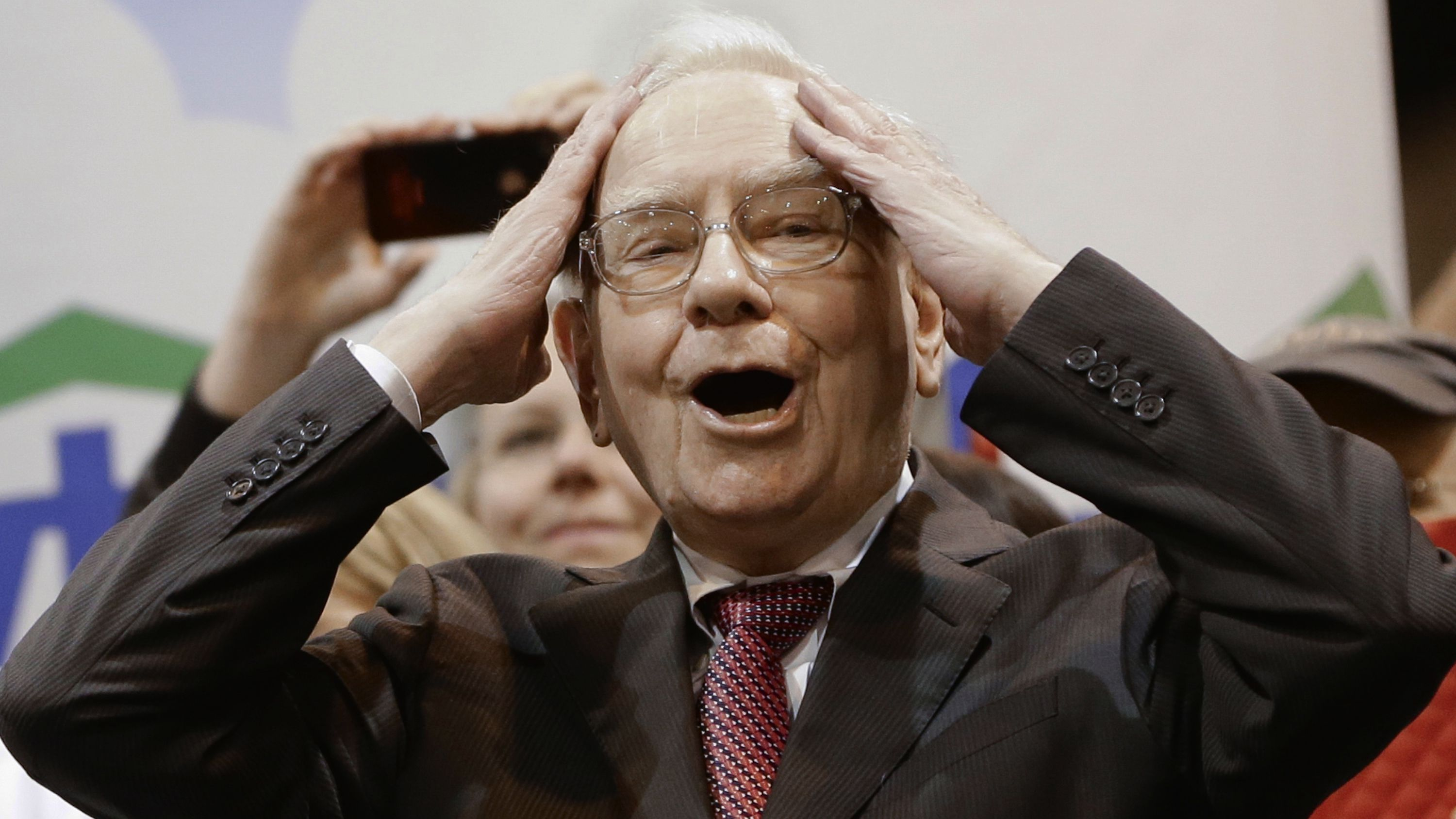 Berkshire Hathaway Chairman and CEO Warren Buffett reacts at the newspaper throwing competition while touring the exhibition floor prior to the annual shareholders meeting on Saturday, May 3, 2014, in Omaha, Neb. More than 30,000 shareholders are expected to fill the CenturyLink Arena to hear Buffett and Berkshire Vice Chairman Charlie Munger discuss their business. (AP Photo/Nati Harnik)