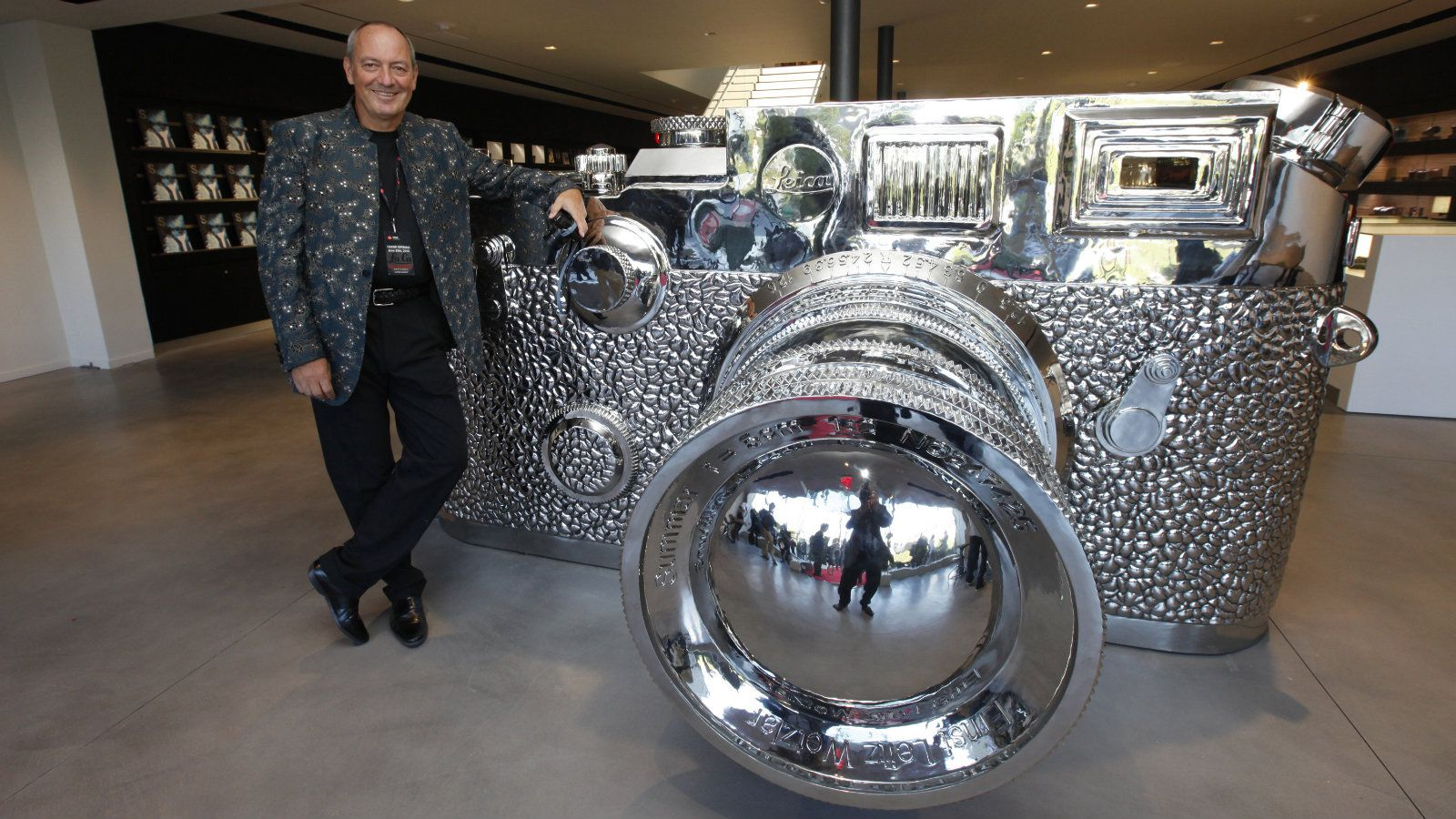 """Chief Executive Officer of Leica Alfred Schopf poses next to a sculpture of a large silver Leica camera by Chinese artist Liao Yibai titled """"Fake Leica,"""" at the launch of the Leica Store Los Angeles in Los Angeles June 20, 2013. The store features three floors of a gallery, retail space and library and the company's high-end still cameras. Picture taken June 20, 2013. REUTERS/Fred Prouser (UNITED STATES - Tags: ENTERTAINMENT SOCIETY)"""