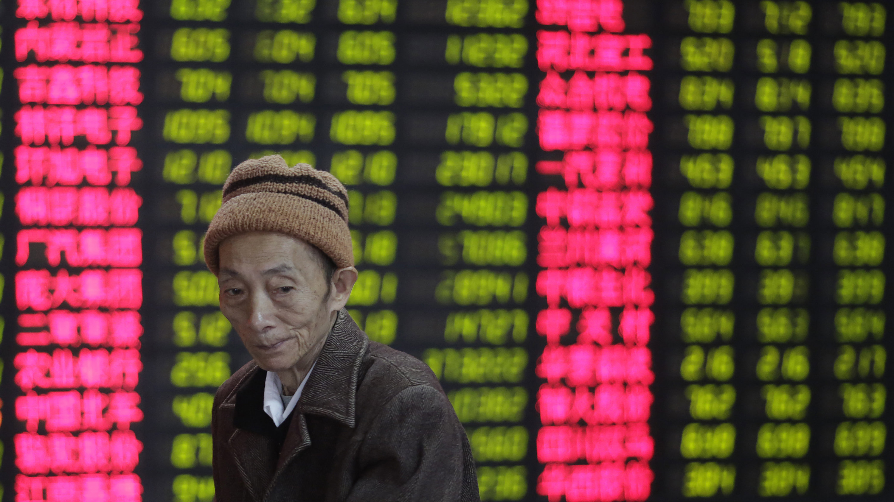 An investor looks at the stock price monitor at a private securities company in Shanghai, China.