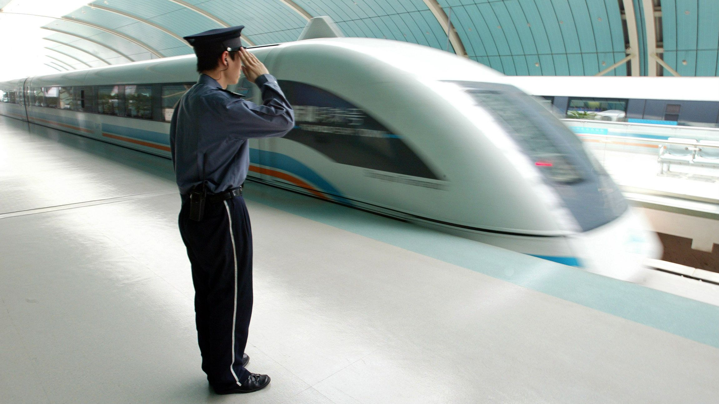 A Chinese security personnel salutes from the platform, next to a maglev train in Shanghai  May 23, 2006. German Chancellor Angela Merkel on Tuesday toured the Shanghai control room of a high-speed train that showcases German magnetic levitation technology, touting cooperation with China but voicing concern about patent piracy. REUTERS/Aly Song