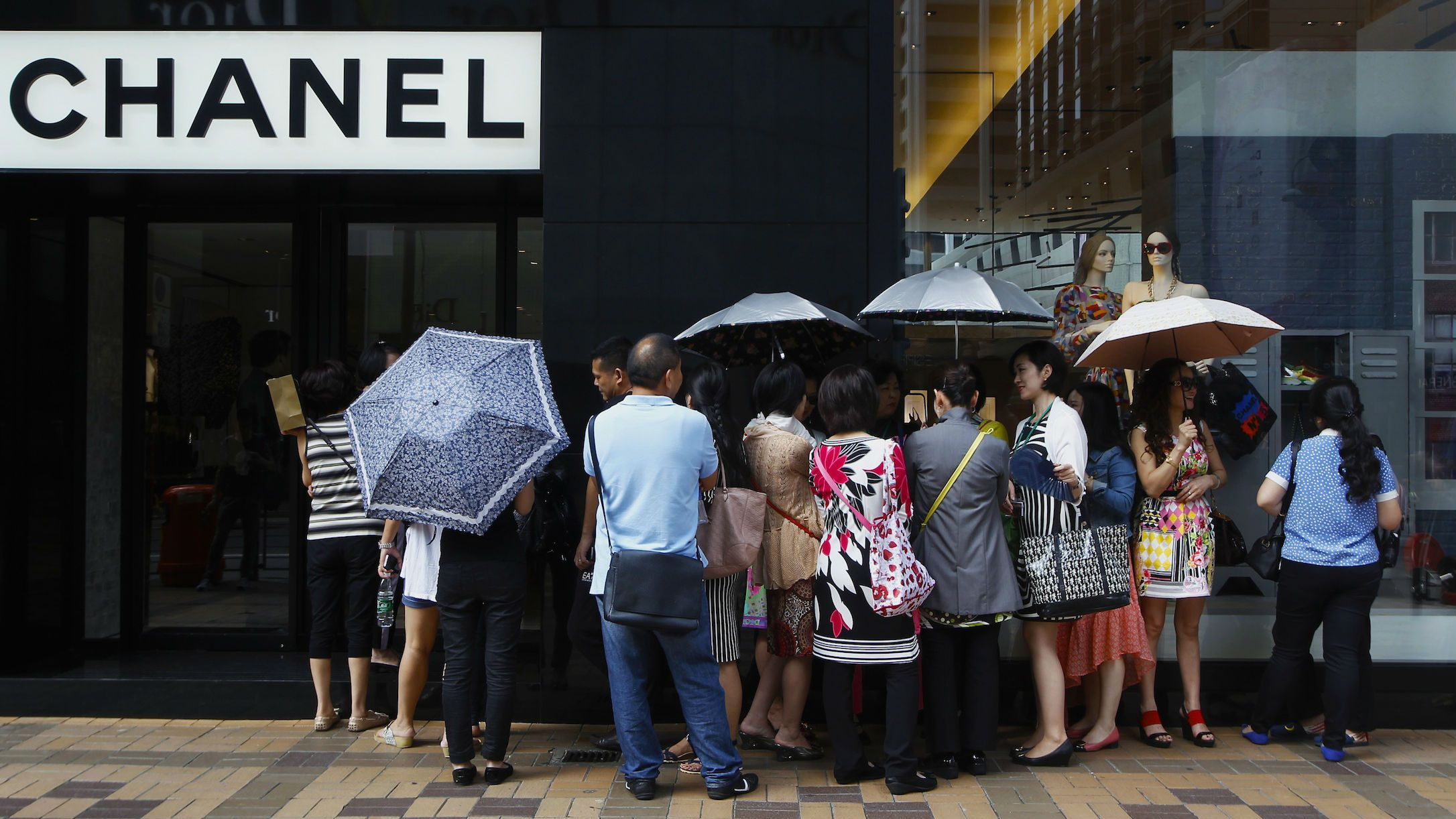 Mainland Chinese tourists wait outside a Chanel store at Hong Kong's Tsim Sha Tsui shopping district October 1, 2014, with part of it being blocked by protesters.