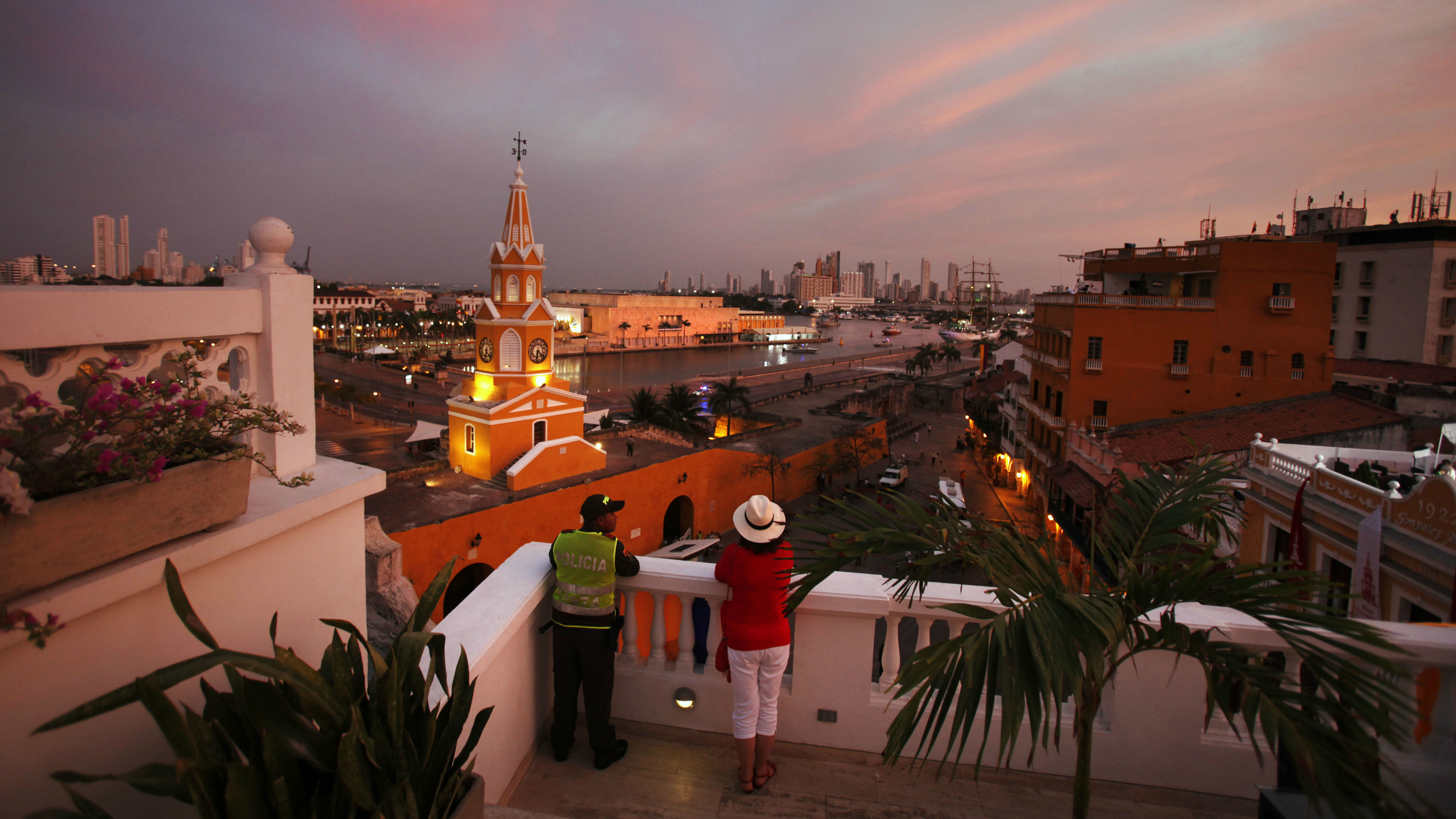 A policeman and a tourist watch the sunset during the Summit of the Americas, being held in the Convention Center, the white building at center, being attended by U.S. Secretary of State Hillary Rodham Clinton and President Barack Obama, in Cartagena, Colombia, on Saturday, April 14, 2012. (AP Photo/Jacquelyn Martin, Pool)