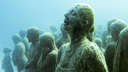 Coral covered statue of some humans