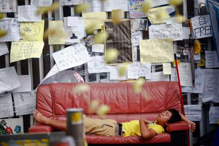 A pro-democracy protester sleeps under messages of support in a protesters' encampment in Hong Kong's financial central district October 28, 2014. Hong Kong has been roiled by a tenacious, month-long student-led people's movement demanding full democracy in the former British colony that returned to Chinese rule in 1997. REUTERS/Damir Sagolj (CHINA - Tags: POLITICS CIVIL UNREST) - RTR4BTX2