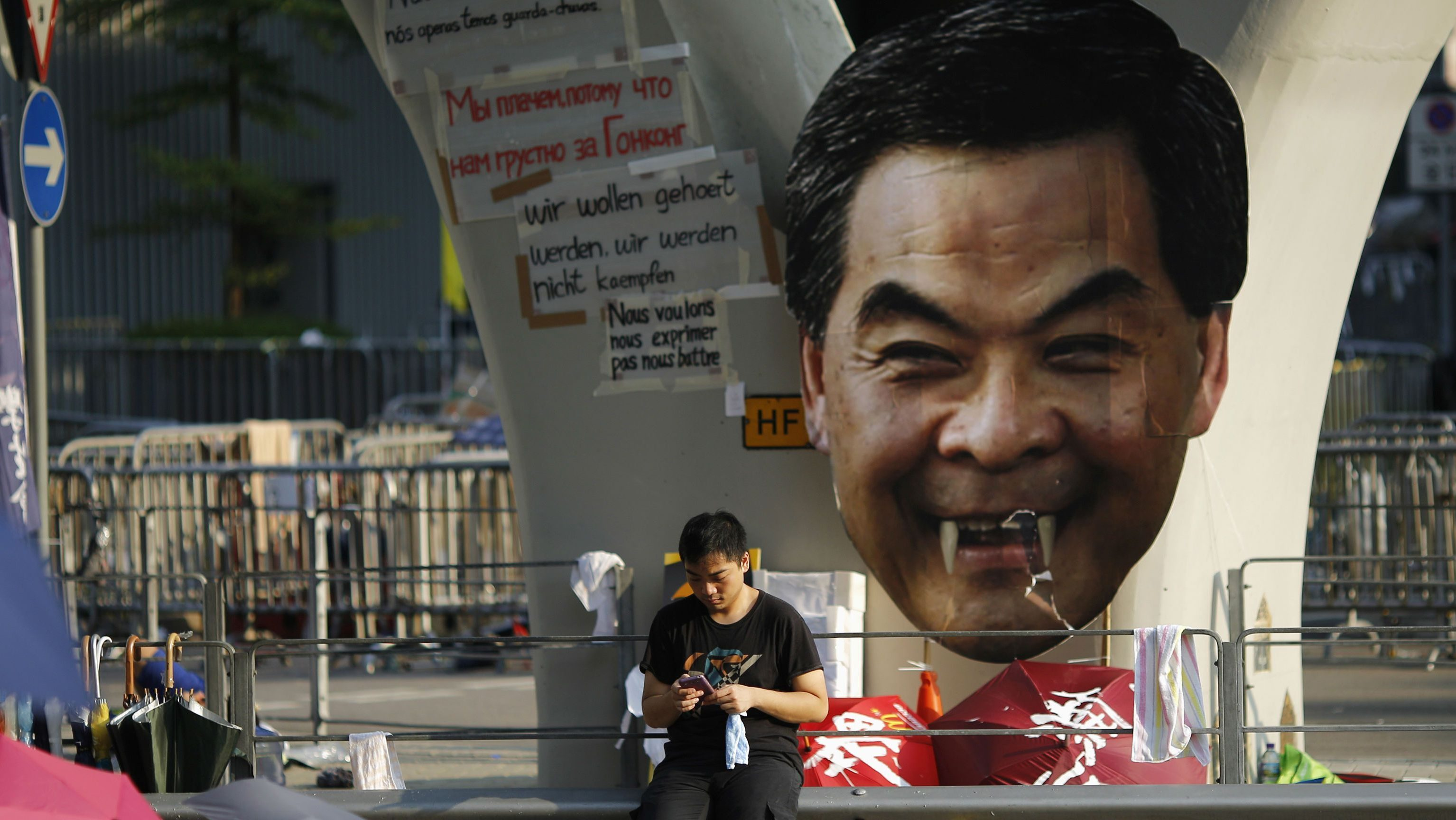 A protester sits next to a defaced cut-out of Hong Kong Chief Executive CY Leung  while blocking a street outside the government headquarters.