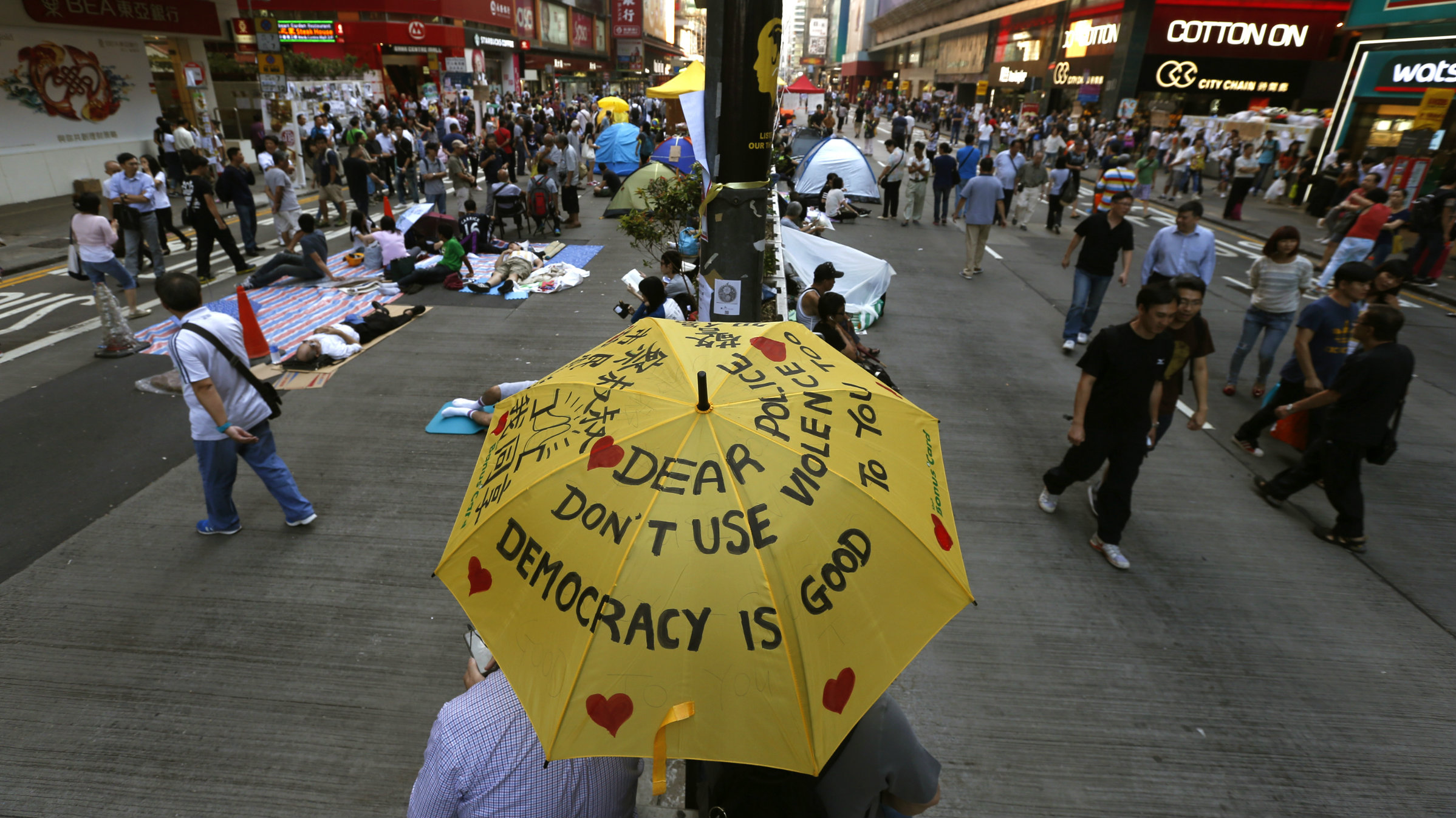 Pro democracy protesters in Hong Kong sit under a yellow umbrella.