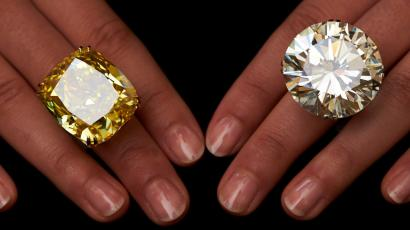 A model poses with a vivid yellow 100.09 carats diamond (L) and a 103.46 carats diamond ring during an auction preview at Sotheby's in Geneva May 7, 2014. These items are expected to reach between CHF 13,250,000 to 22,250,000 (USD 15,000,000 to 25,000,000) and CHF 3,100,00 and 4,450,000 (USD 3,500,00 to 5,000,000) when they go on sale May 13, 2014 in Geneva.