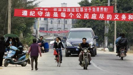"""Residents pass under banners which reads """"Obeying the law is every citizen's duty and responsibility"""" and """"Recognize the truth, insist on separating from unlawful members"""" at the entrance to Dongzhou village near Shanwei, Guangdong, Southern China, Wednesday, Dec. 14, 2005."""